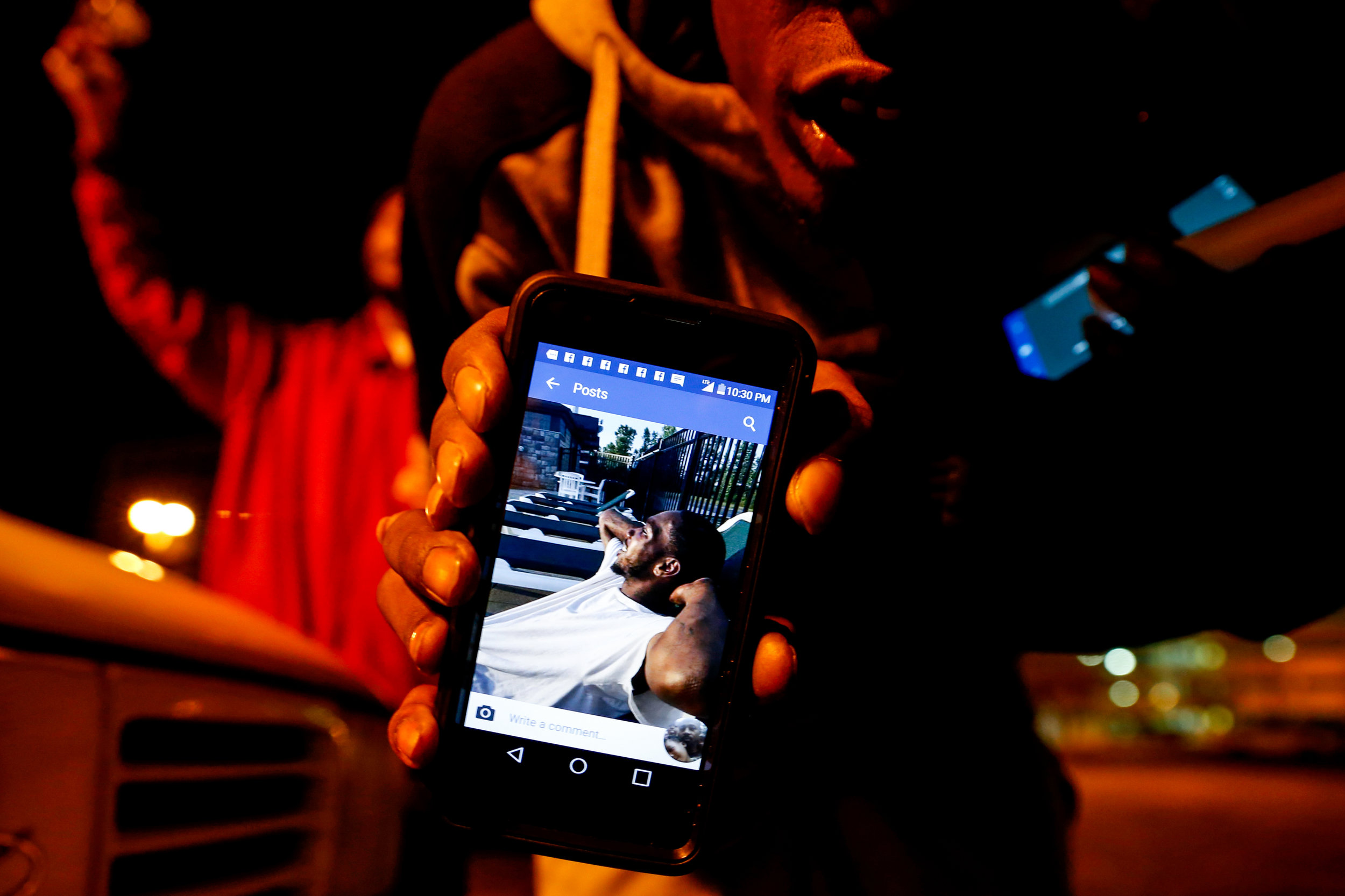 "Chola Williams, brother of Donte Williams, holds up one of his favorite pictures of Donte while gathered at a vigil service on Sunday, Oct. 23, 2016 at the Flat Lot in downtown Flint where he died earlier that day after being shot multiple times. ""That's Donte looking at us right now,"" Williams said as he shows a photo of his brother from his phone."