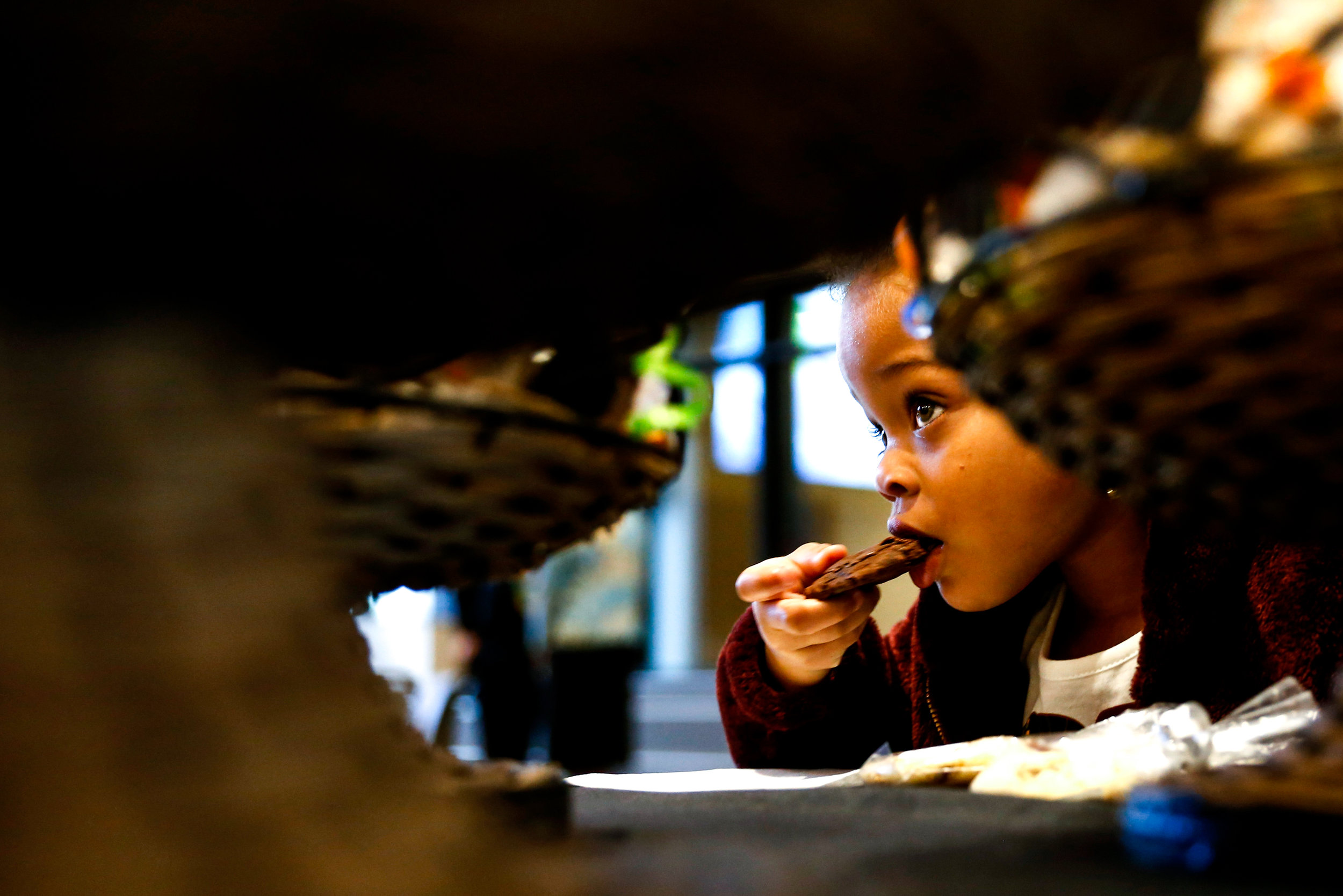 Armani Searcy, 4, of Flint, enjoys a cookie while attending the ribbon cutting ceremony of a completed construction project at the Genesee Career Institute with her father Derrick Searcy on Wednesday, Oct. 26, 2016 in Mundy Township. The event offered an opportunity for those in attendance to tour the facility and learn about different programs for students.