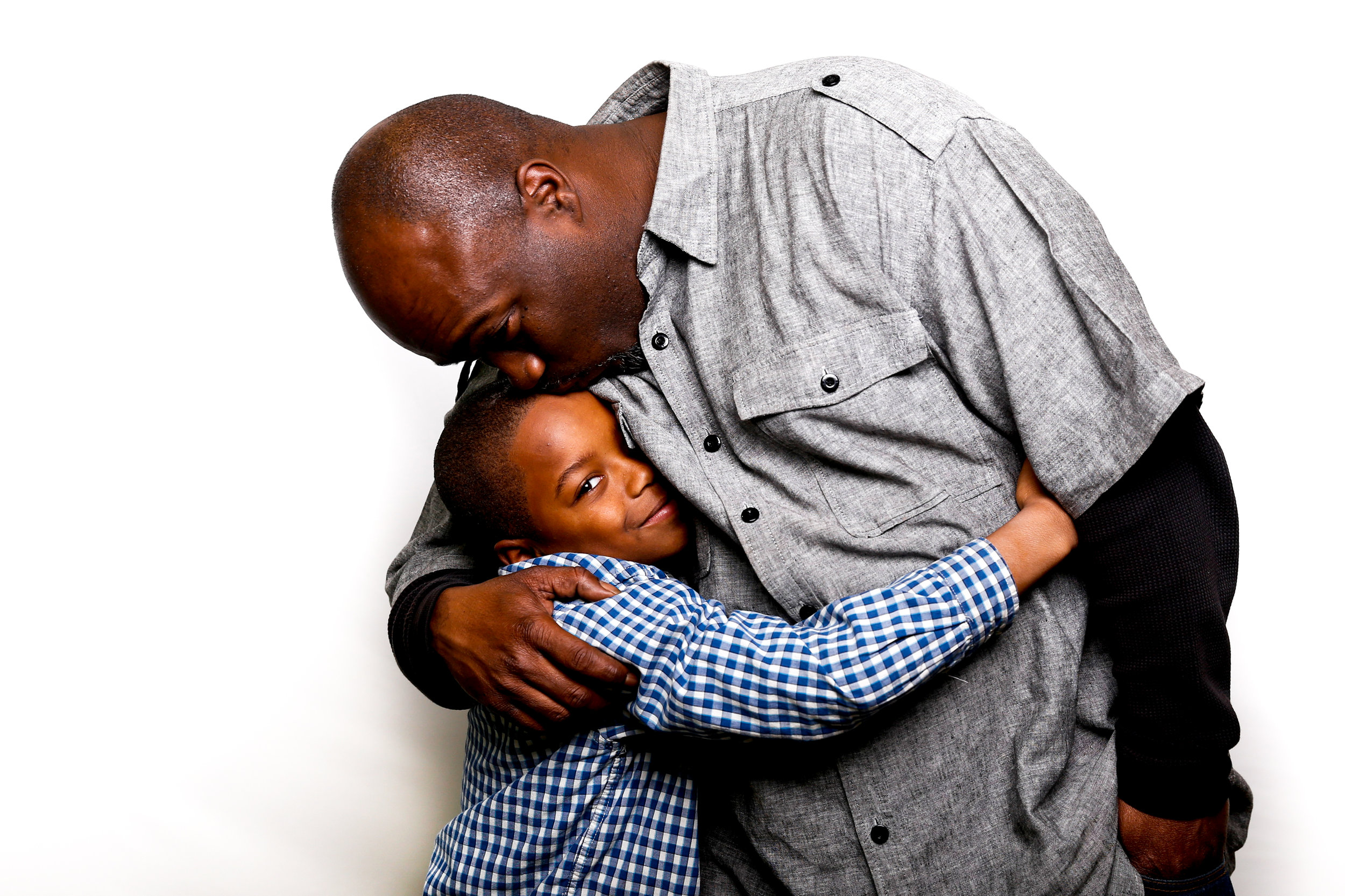 Dei'on Wright, of Flint, hugs his father Moe during a free holiday portrait on Wednesday, Dec. 14, 2016 at The Flint Journal in downtown Flint. To them, the holiday season means family and sharing.