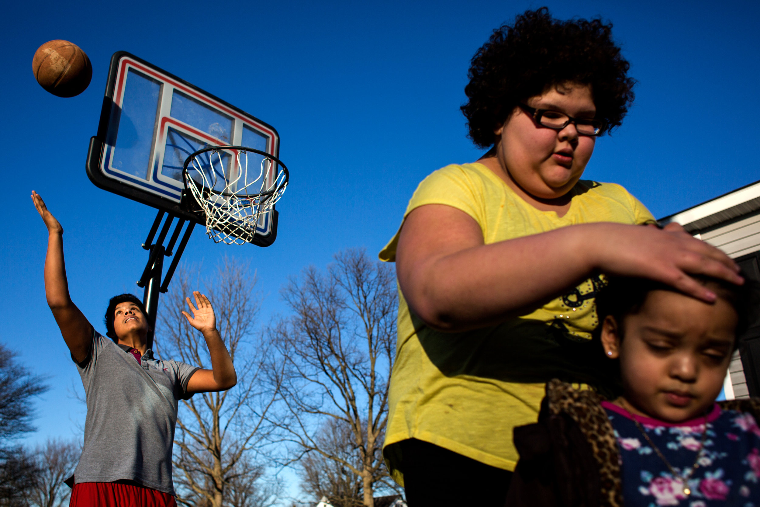 Melvin Orellana, 15, left, caught a rebound while his sister Margery Villalta, 11, tied up the hair of their cousin Cinita Lopez, 3, all of Huntingburg, on Wednesday afternoon outside their home in Huntingburg. The cousins took advantage of this week's unseasonably warm weather — Wednesday's highs reached into the 60s — and played outside.