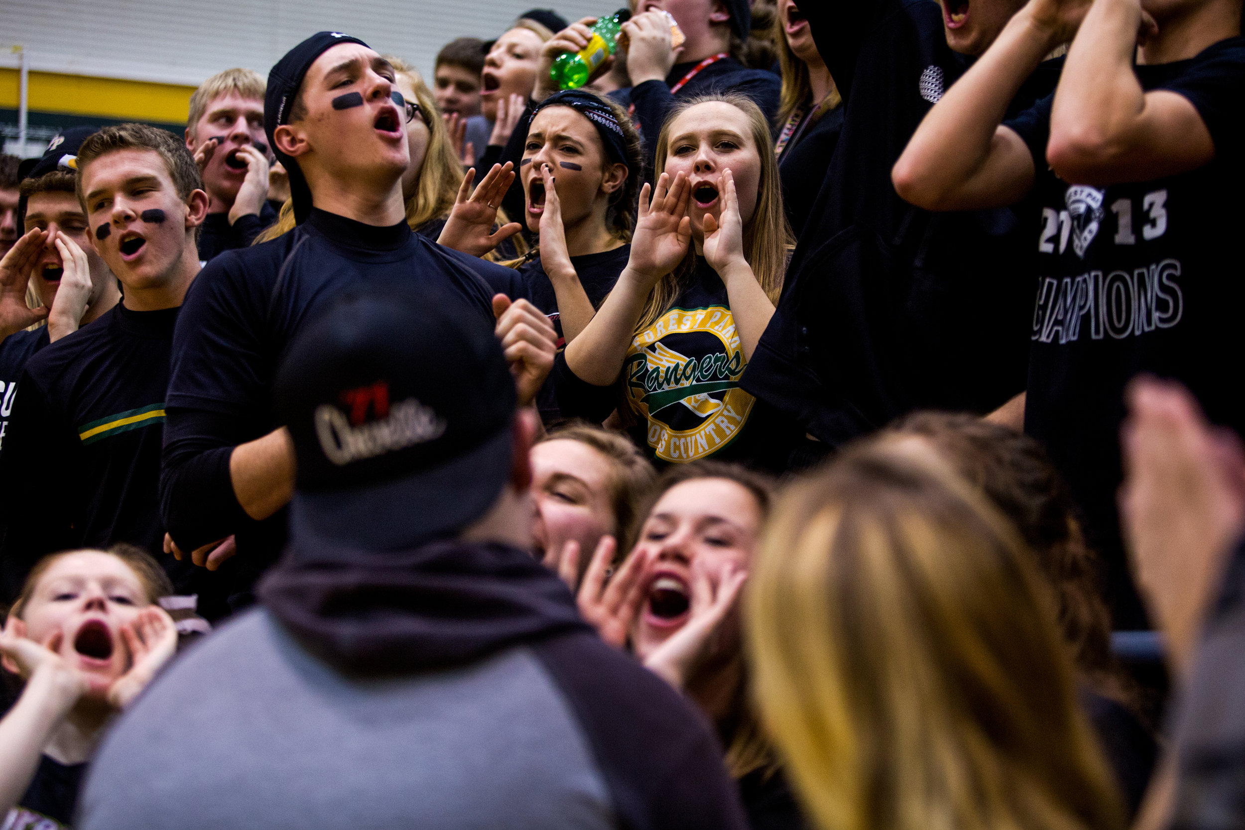 Aliya Haake of Ferdinand, 18, center, stood next to Anna Bailey of Ferdinand, 17, left, while cheering in the student section during Friday night's basketball game at Forest Park High School in Ferdinand. Forest Park defeated South Spencer 62-46.