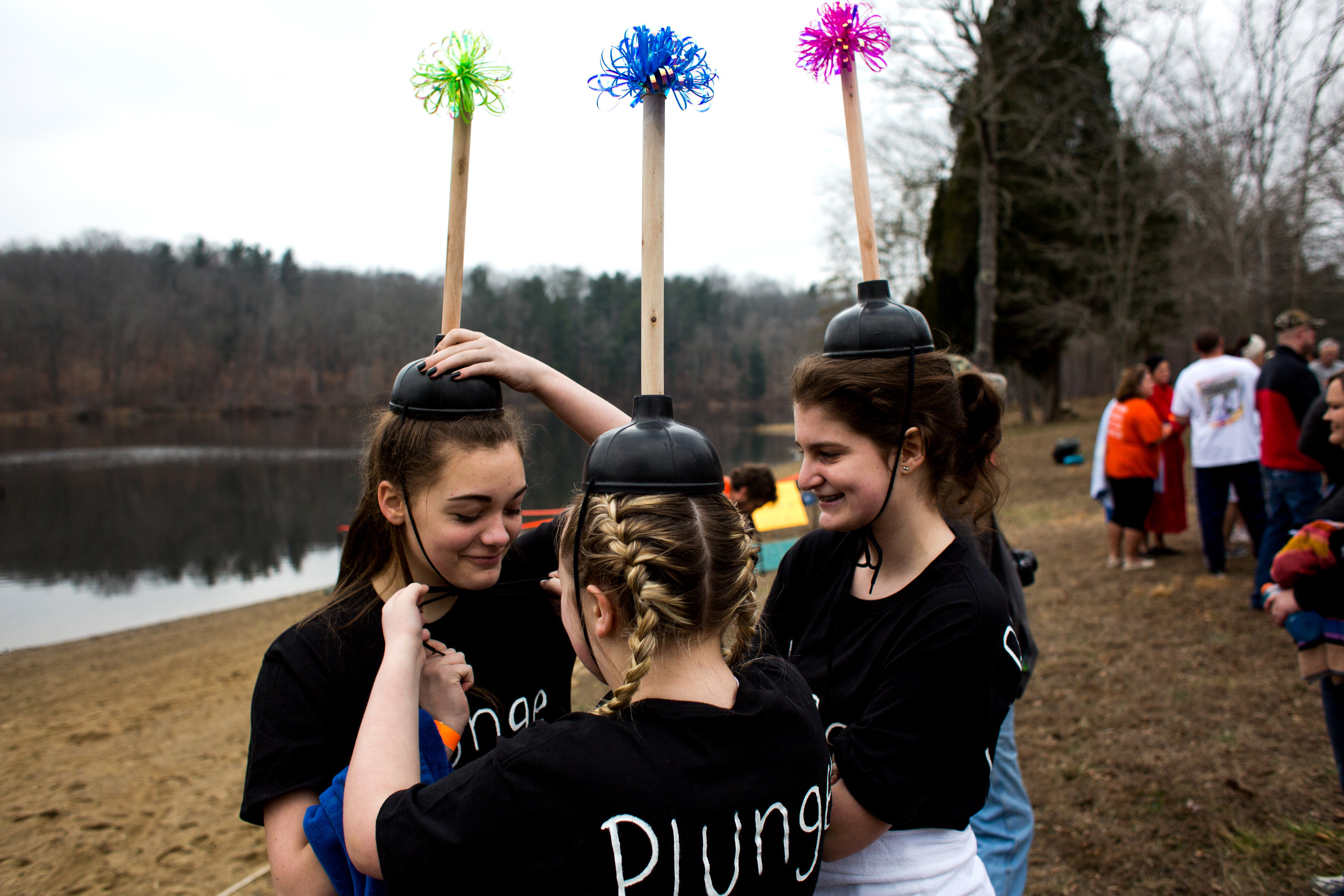 Gracie Graves of Ferdinand, 13, middle, secured a plunger hat on Kristen Detty of Birdseye, 13, before participating with Kendall Barth of Ferdinand, 13, right, in the annual Plunge for Dubois County on Sunday afternoon at Ferdinand State Forest in Ferdinand. Proceeds from the event benefited the Lange-Fuhs Cancer Center, Dubois County Leukemia Association and area food banks.