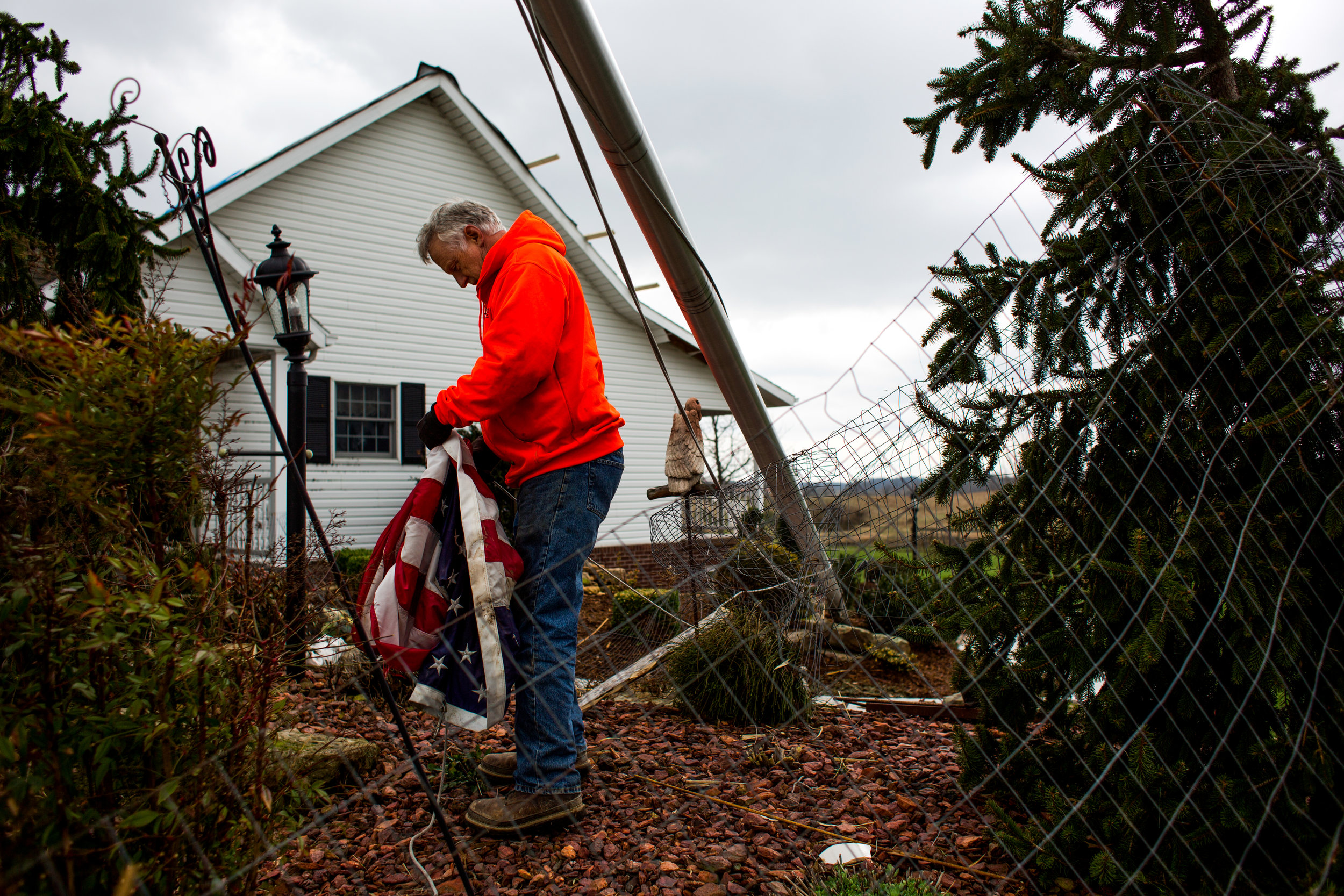 "Lenny Marks of Jasper picked up a flag from a fallen flag pole Wednesday morning outside the home of his friend, Sam Schwenk, in Ireland. Marks helped salvage items and clear debris after a tornado hit and damaged Schwenk's home and barn. ""All my keepsakes blew away,"" Schwenk said. ""I'm still in a state of shock."""