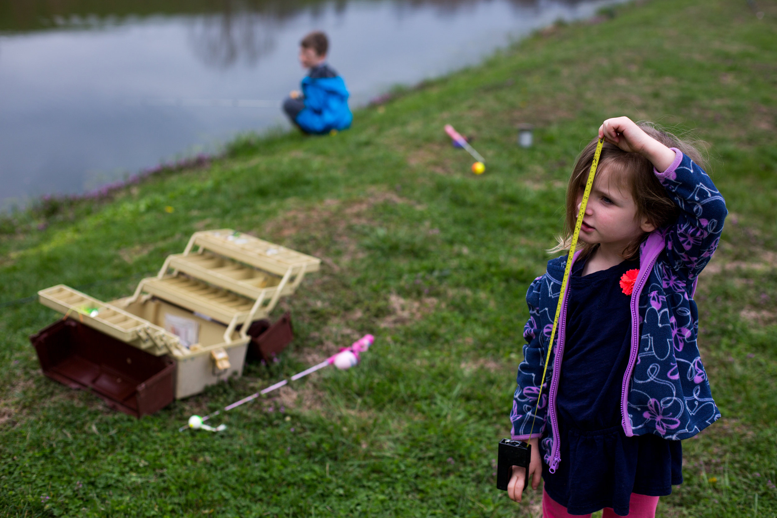 Molly Schepers of Dubois, 4, asked for help in measuring herself while her brother Marshall, 8, fished at their grandmother's pond in Dubois on Tuesday.
