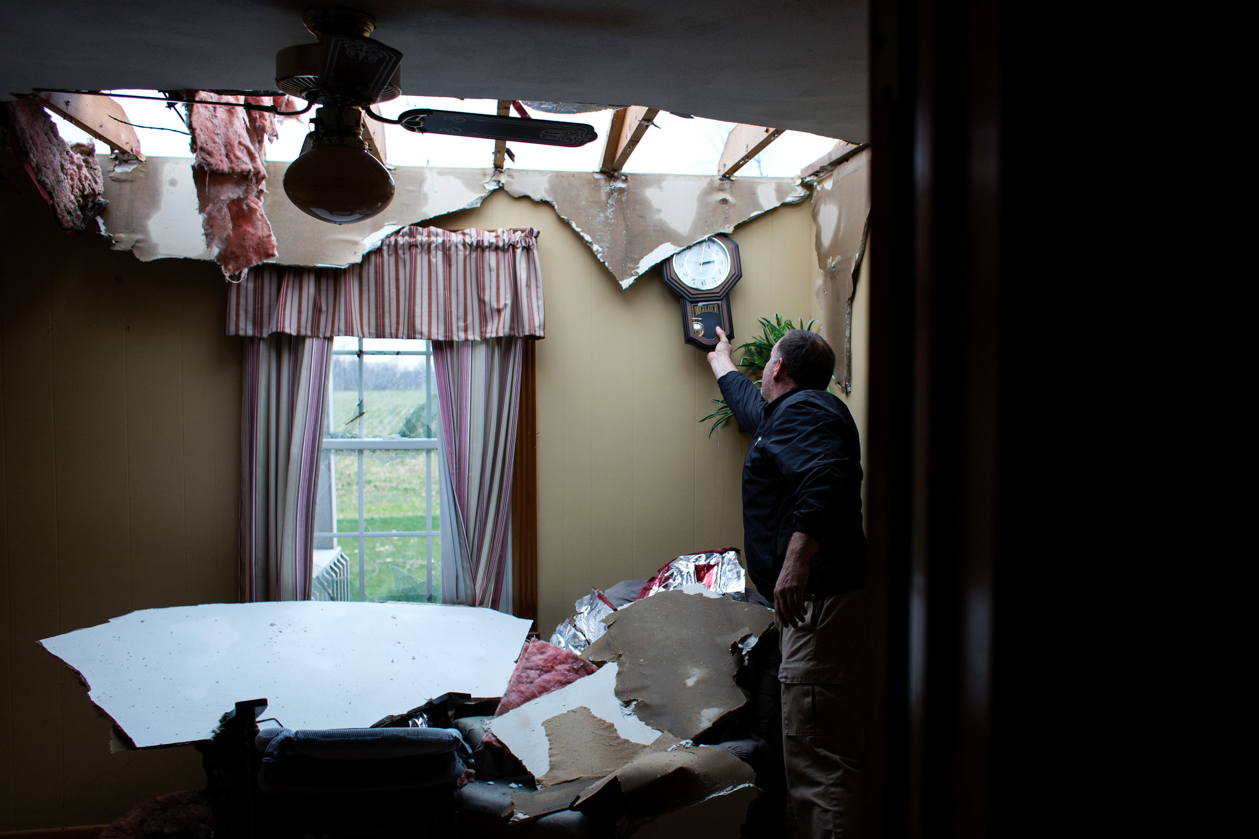 David Main of Jasper took a clock from the wall while collecting salvageable items after a tornado destroyed the home of his friends, Ed and Kathy Vollmer, Wednesday, March 1, 2017, in Ireland.