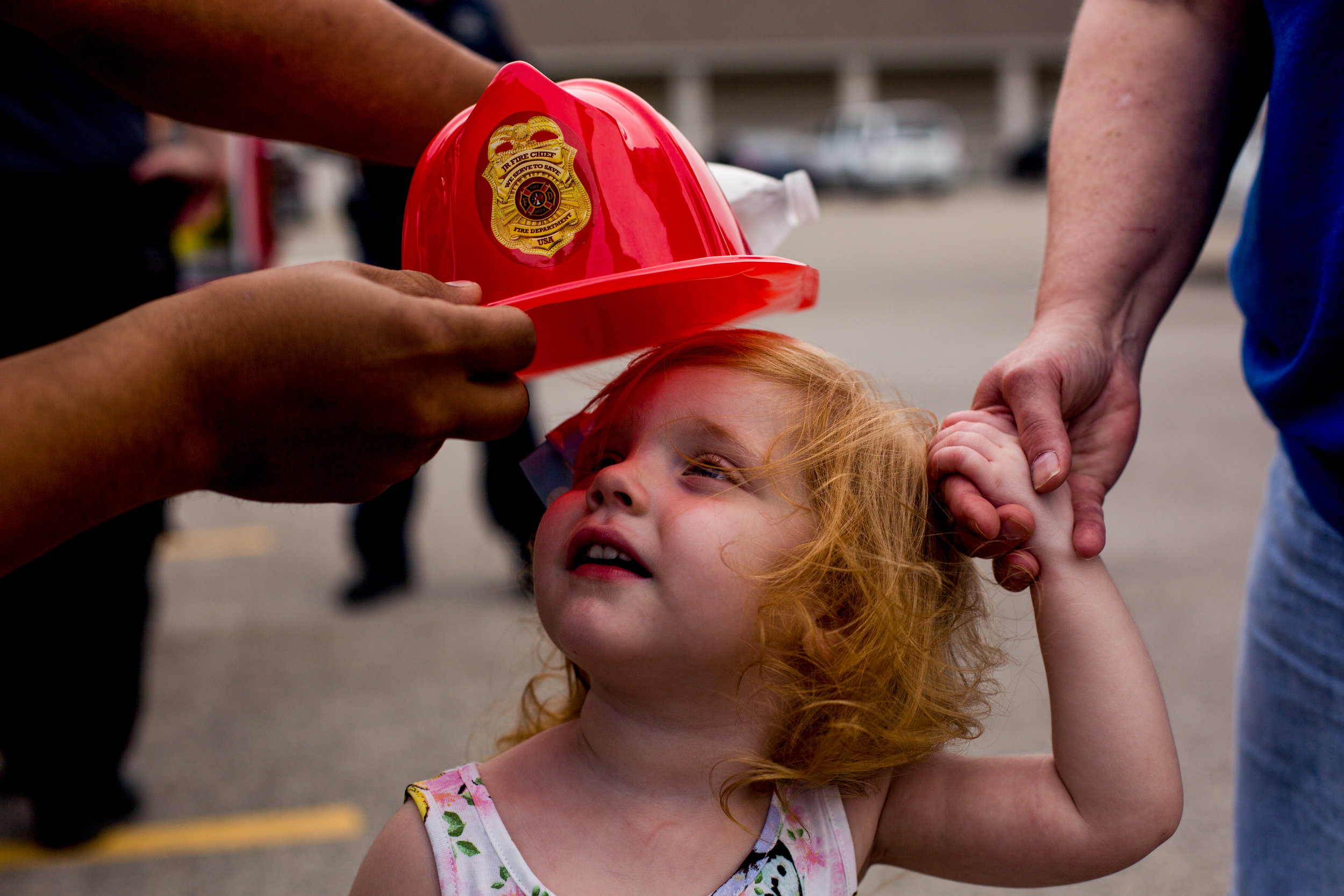 Lauren Pitrowski of Jasper, 2, held the hand of her grandmother, Jeannine Martin of Jasper, as a Jasper firefighter tried to place a hat on her head during the Fifth Street School Community Health Fair on Thursday in Jasper. More than 30 vendors set up at Fifth Street to promote healthy living with nutritious snacks and several activities for families to enjoy.
