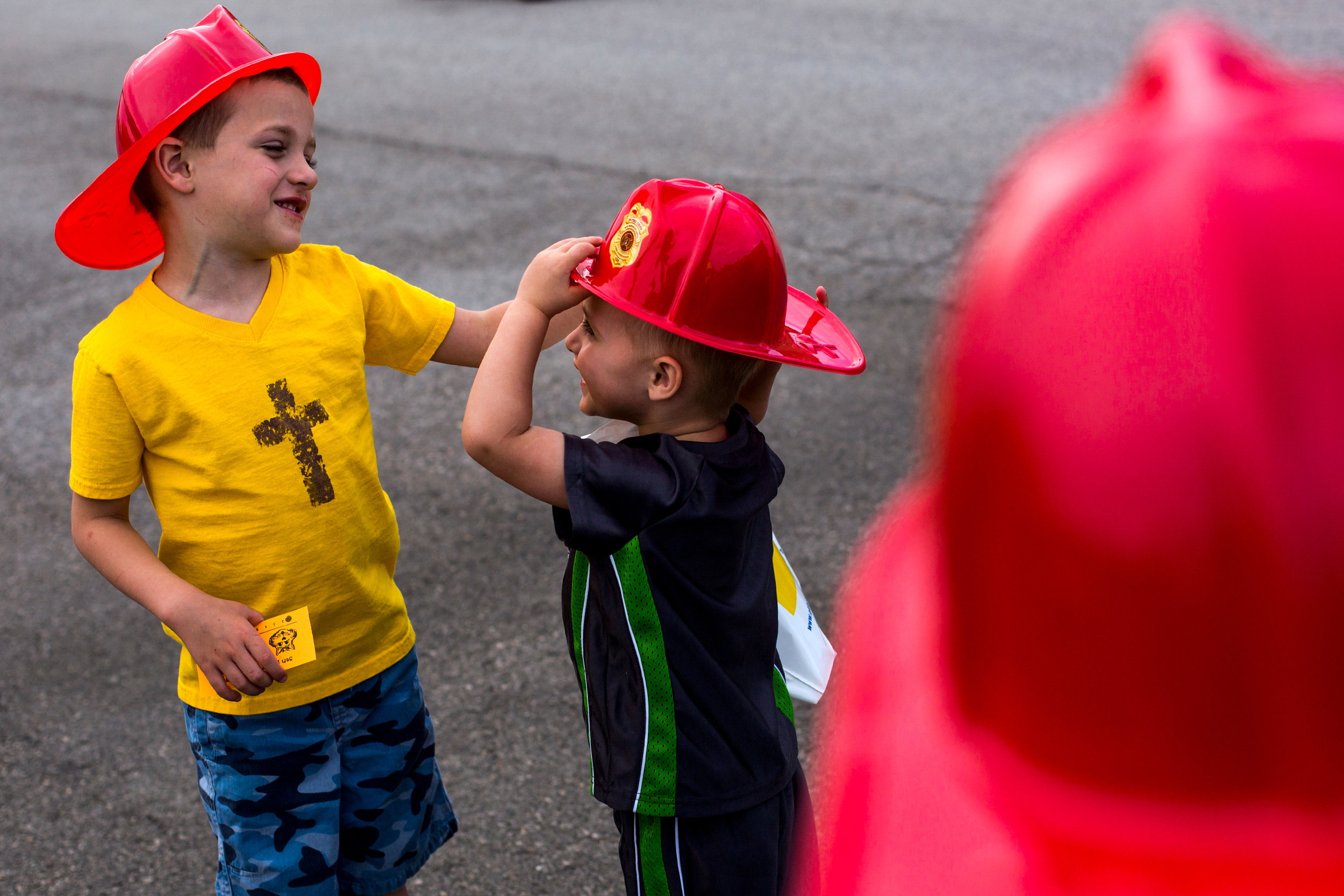Grant Gehlhausen of Ireland, 8, watched his younger brother, Cash, 4, left, help Max, 2, adjust the hat he received from the Jasper Volunteer Fire Department during the Fifth Street School Community Health Fair on Thursday in Jasper. More than 30 vendors set up at Fifth Street to promote healthy living with nutritious snacks and several activities for families to enjoy.
