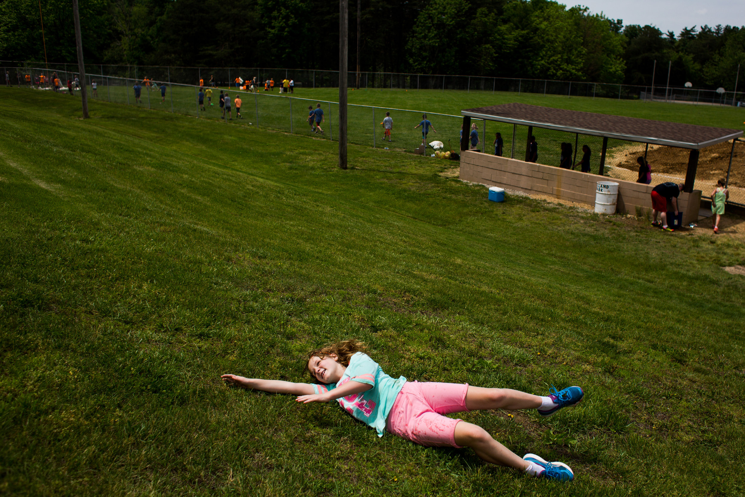 Holland Elementary School fourth-grader Jill Keusch rolled down the hill during the school's field day Wednesday at Holland Park.