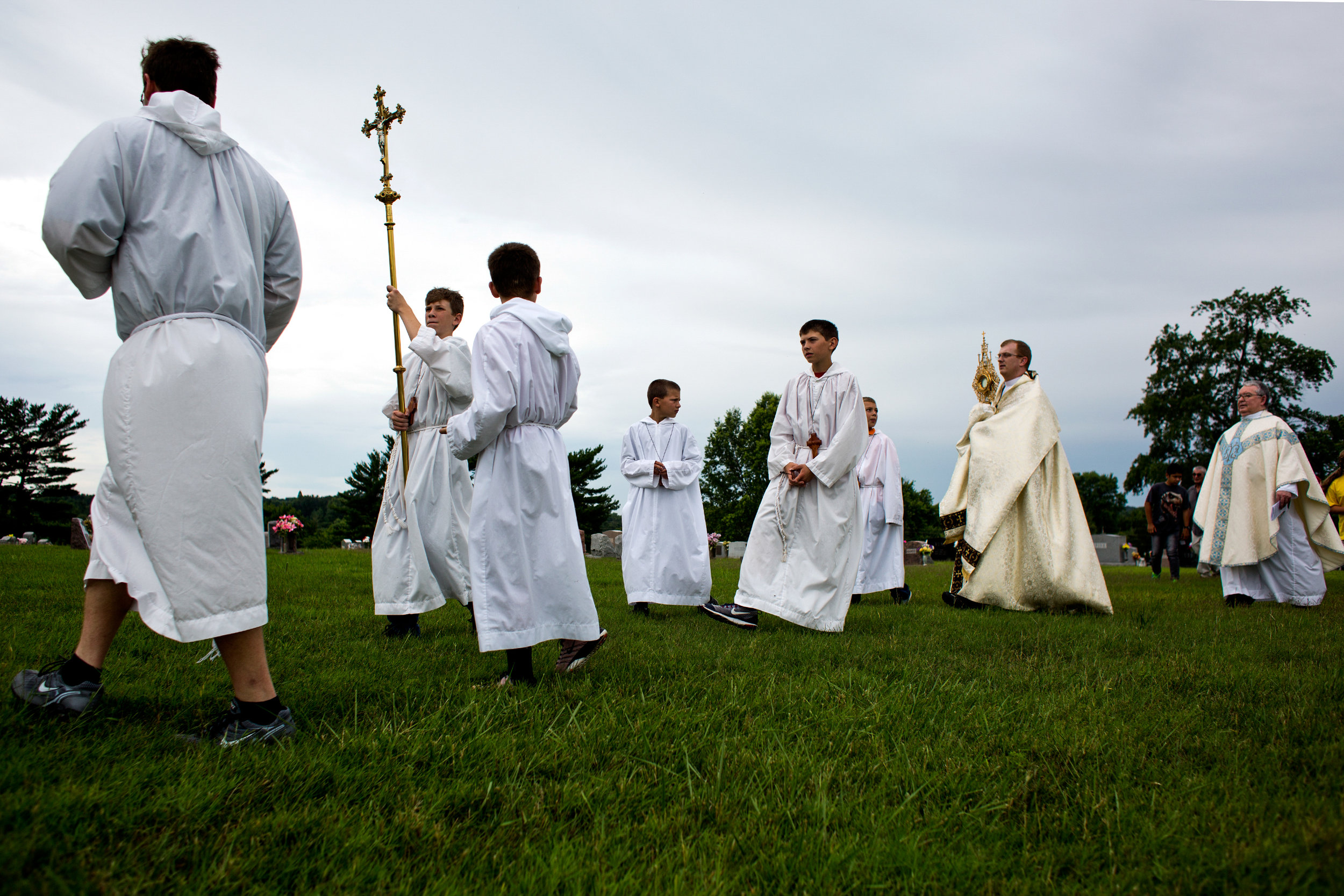 Father Ryan Hilderbrand, second from right, carried the sacrament of monstrance through the cemetery behind St. Mary's Catholic Church to the alter during a Corpus Christi procession Sunday in Huntingburg.