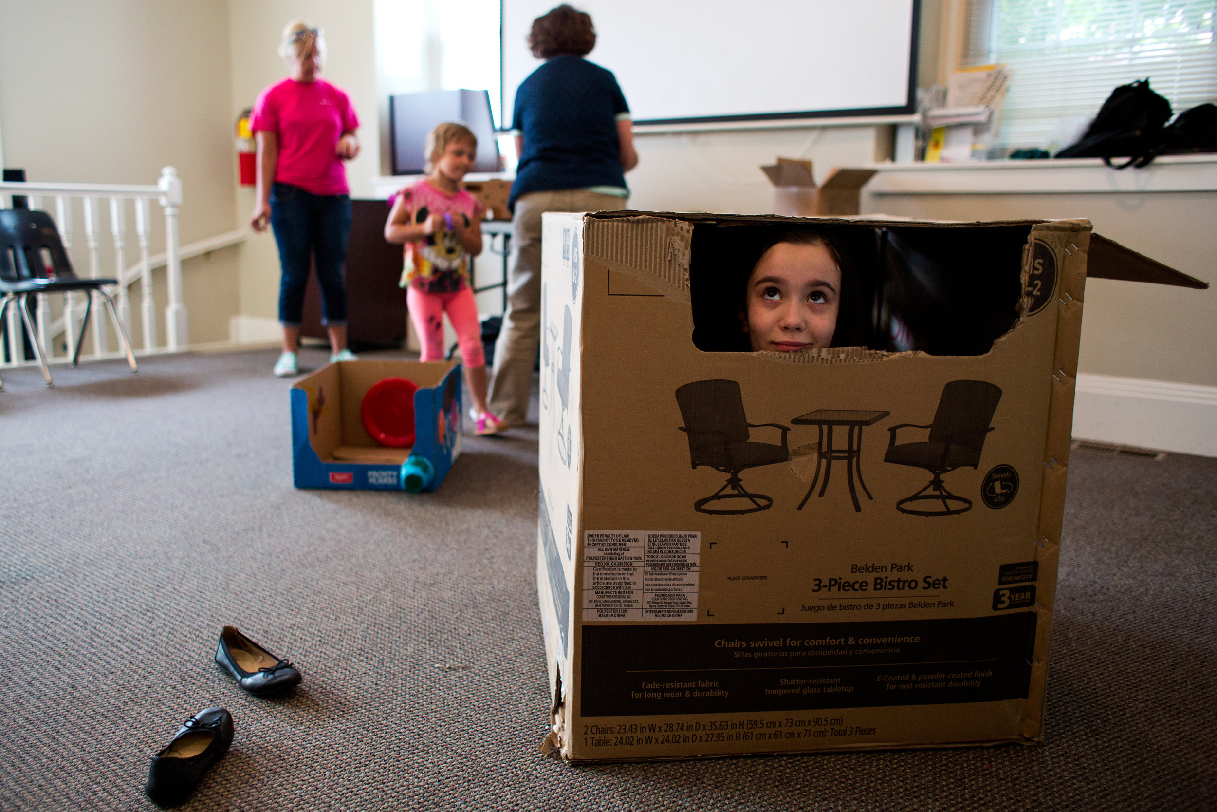 Madeline Zipp-Nathan of Jasper, 9, peeked out of the box she was decorating during Thursday's Cardboard Car Project at the Jasper Library Annex. The library provided paint, stickers, plastic plates, cups and more for children to decorate their boxes.