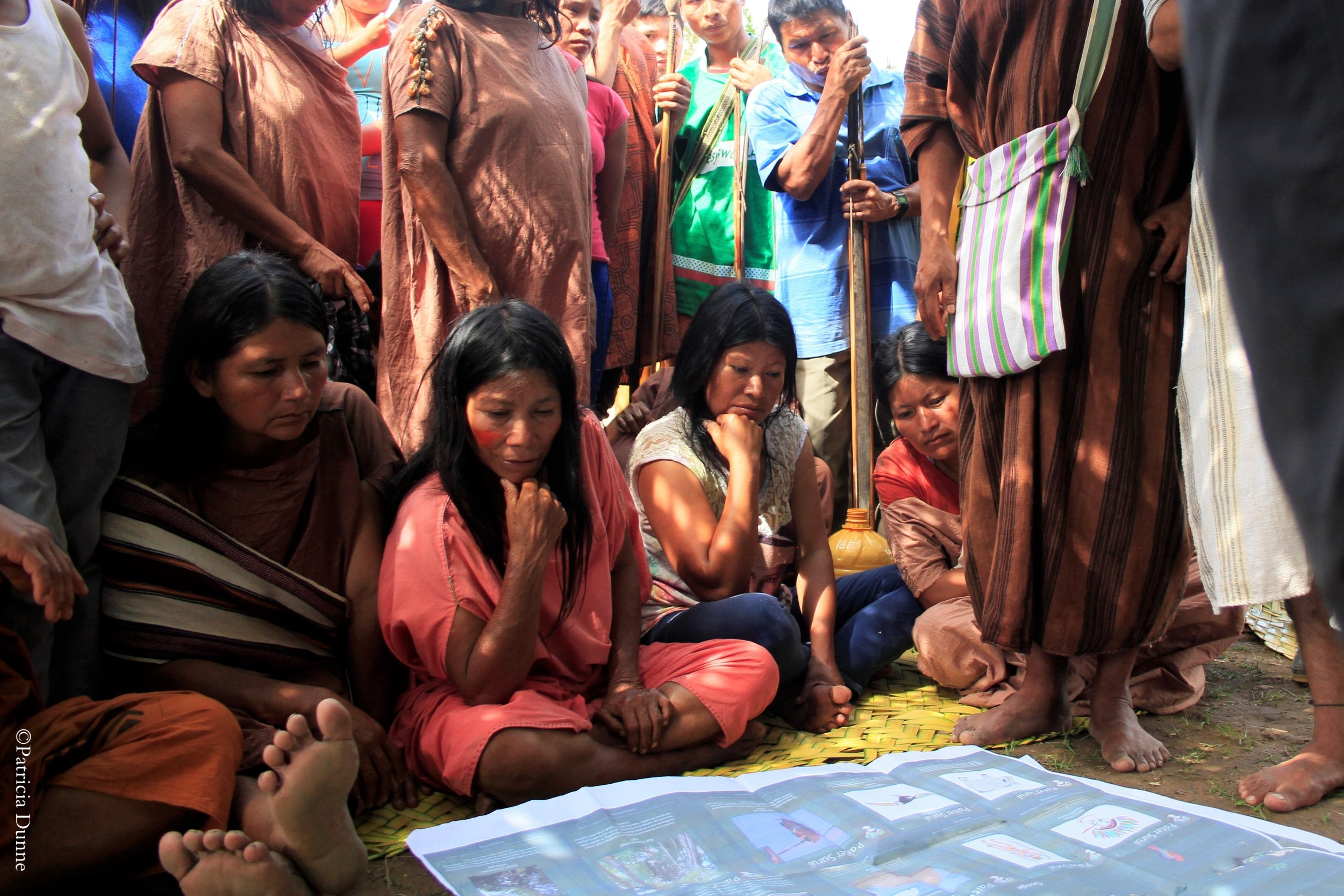 Women in the Palomar community review a cultural map created by the Suri indigenous community in Brazil to digitally record their people's cultural and ecological knowledge.