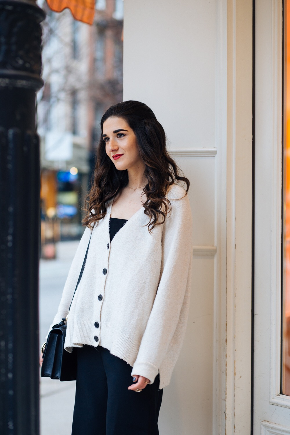 Black Jumpsuit Cream Cardigan All About The Blogger Hierarchy Esther Santer Fashion Blog NYC Street Style Blogger Outfit OOTD Trendy Shoes Booties Ivanka Trump Henri Bendel Bag Sweater Cozy Culottes Hair Model Girls Shopping Wear Winter  Minimal Inspo.jpg