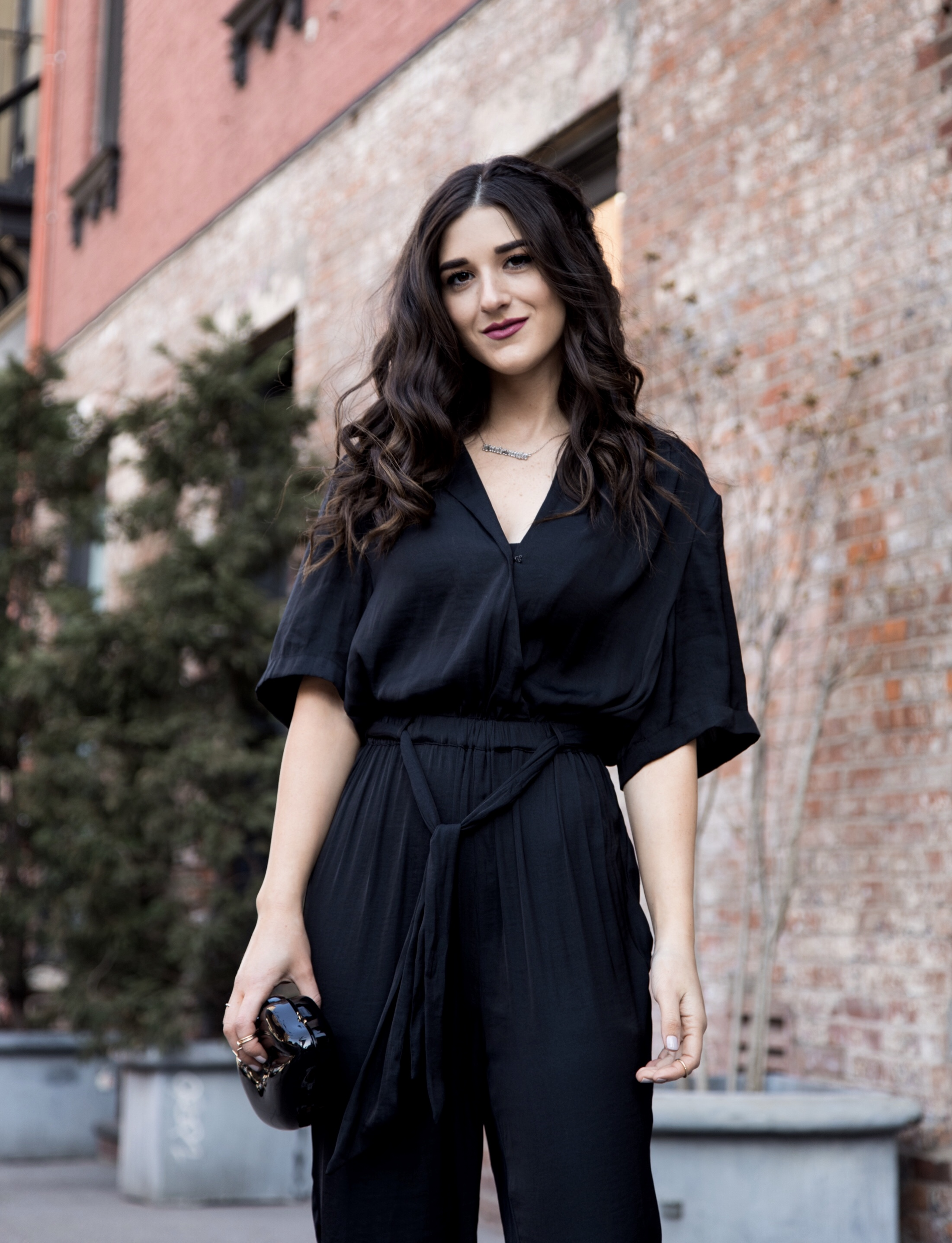 Where We're Going For Our Honeymoon Black Silk Jumpsuit Bow Mules Esther Santer Fashion Blog NYC Street Style Blogger Outfit OOTD Trendy Urban Outfitters Betsey Johnson Soho Collab Jeweled Shoes Earrings Braid Hairstyle Hoops Necklace Lips  Clutch Bag.jpg