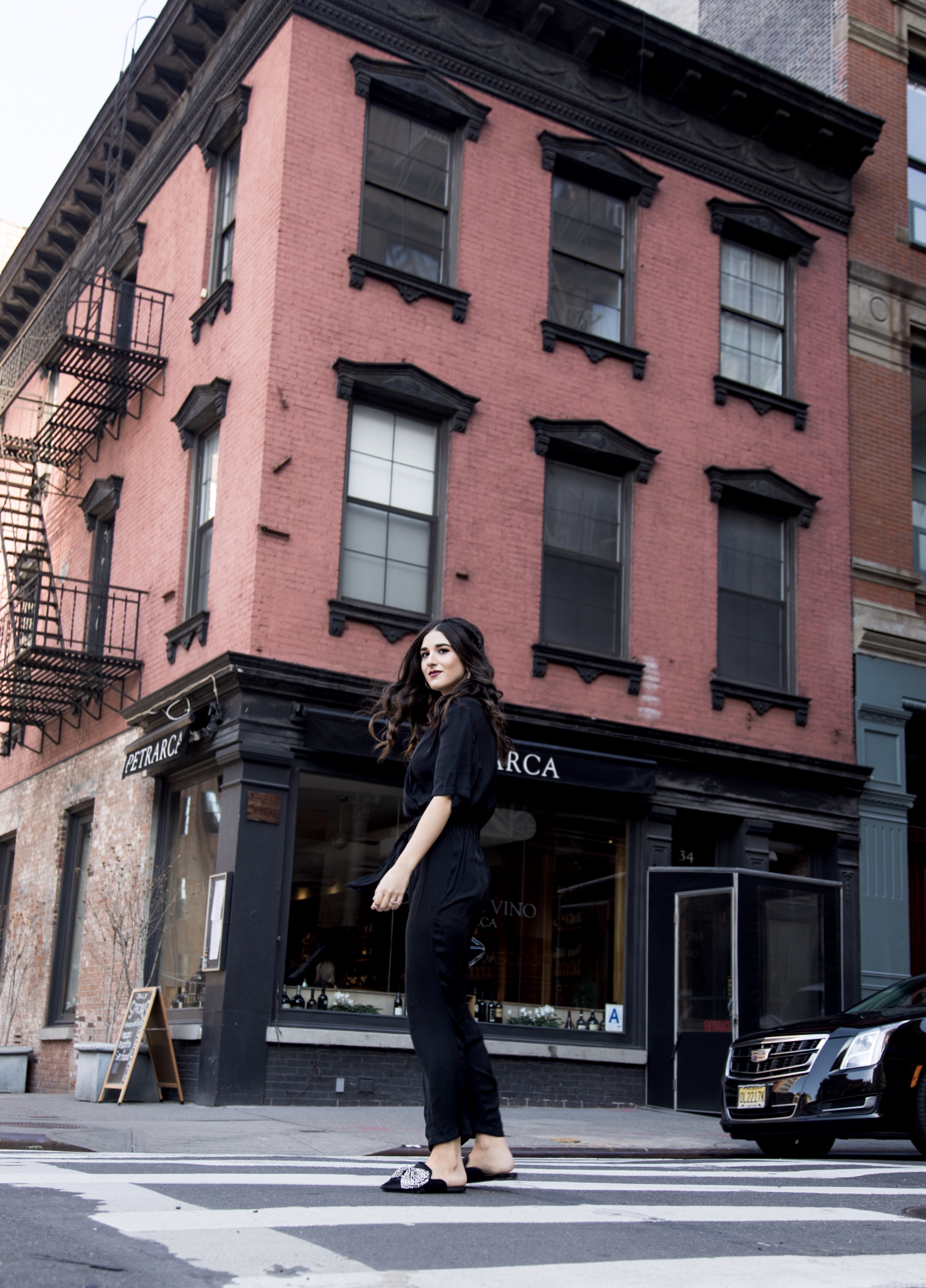 Where We're Going For Our Honeymoon Black Silk Jumpsuit Bow Mules Esther Santer Fashion Blog NYC Street Style Blogger Outfit OOTD Trendy Urban Outfitters Betsey Johnson Brand Collab Jeweled Shoes Earrings Braid Hairstyle Hoops Necklace Lips Clutch Bag.jpg