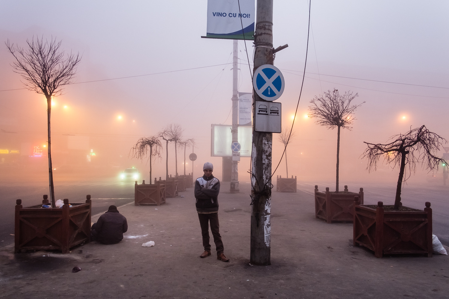 """Wintry sunrise at Gara de Nord. The text """"vino cu noi"""" (""""come with us"""") stands over the head of Azavoae (19, grown up in orphanage until 18). Under the street, the tunnel that used to be """"home"""" to many."""