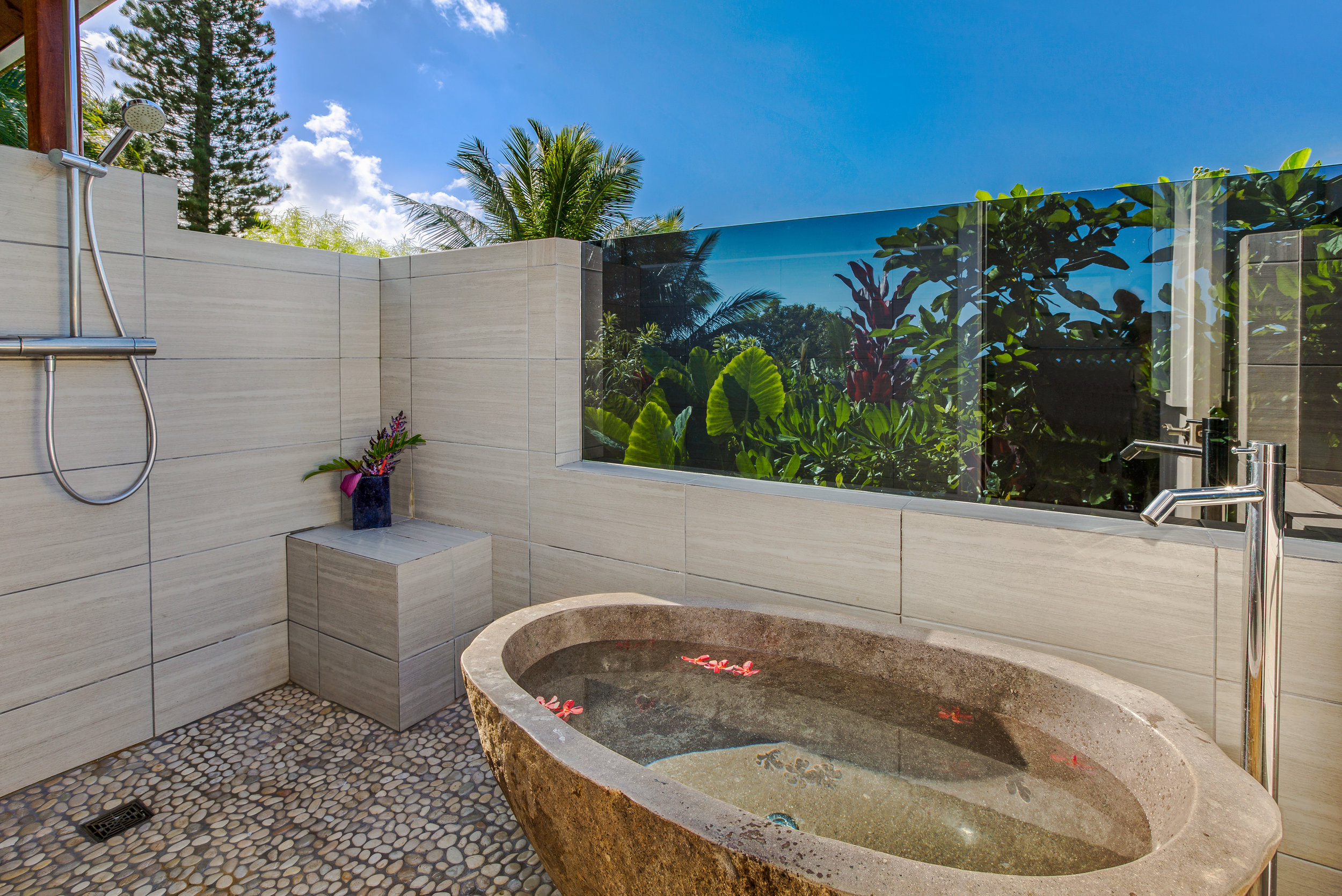 West Master ensuite bathroom outdoor area features stainless steel rain shower and Balinese stone soaker tub, both with ocean views.