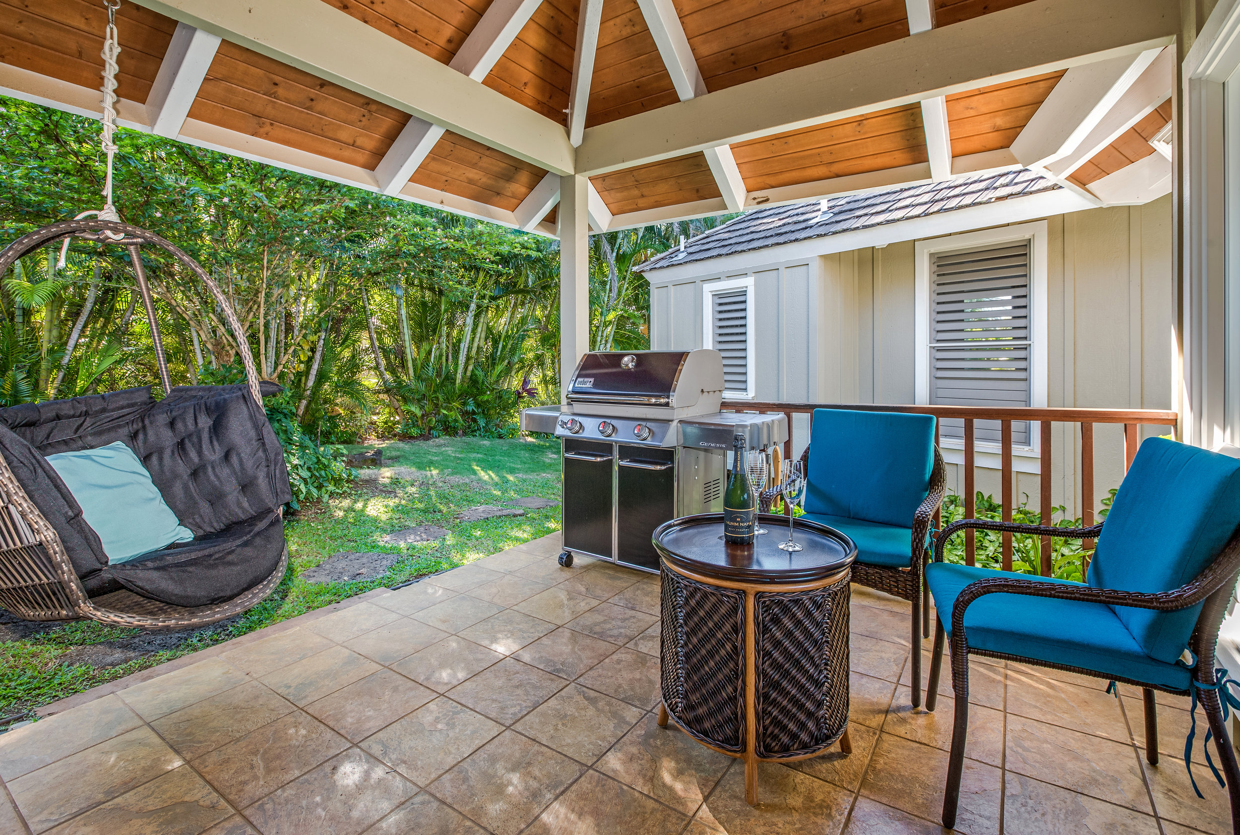 The shaded garden side lanai is the perfect place to relax with a book in the Balinese hanging chair, and to barbecue on the new large gas Weber.