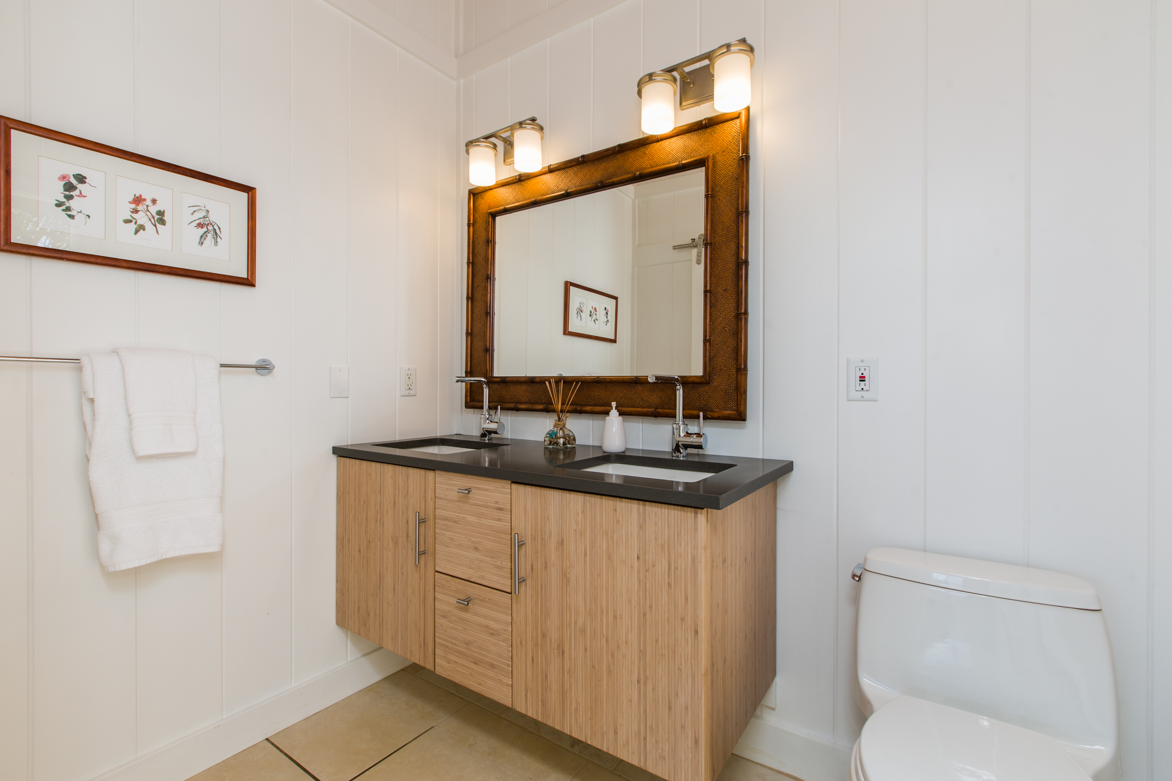 West oceanside master bedroom ensuite, indoor area, features double hanging solid bamboo and quartz vanity and one-piece toilet.  Step outside from here to shower and bathe...