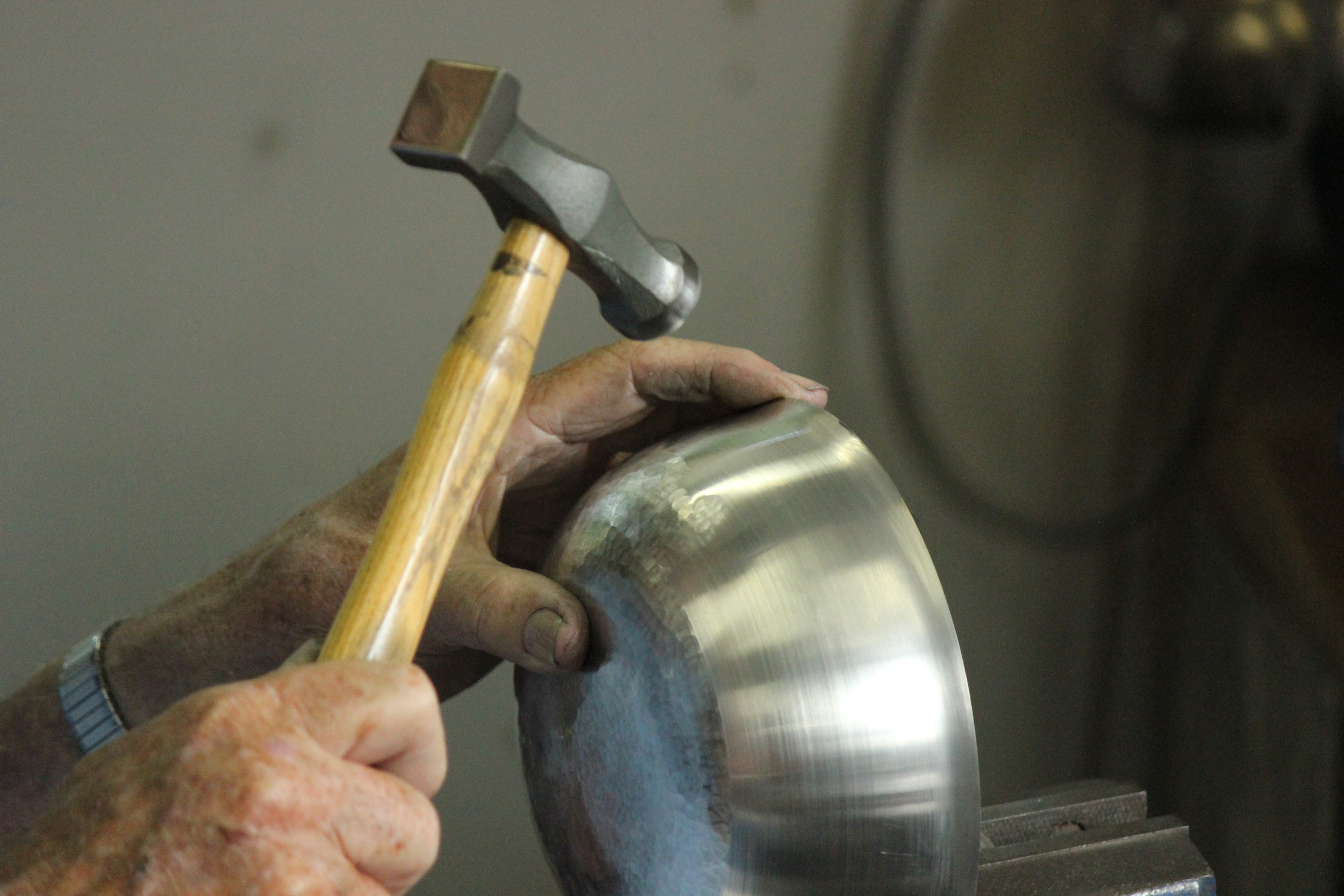 Hammering a pewter bowl in order to achieve a planished finish.