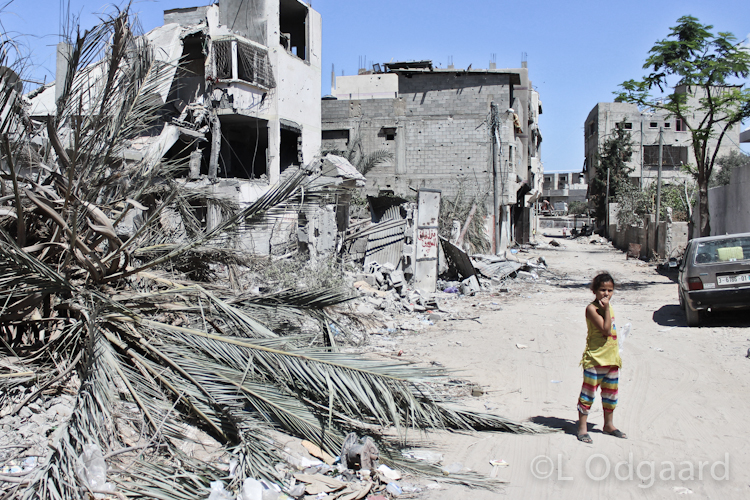 Palestinian girl walking in destroyed Shejaiya