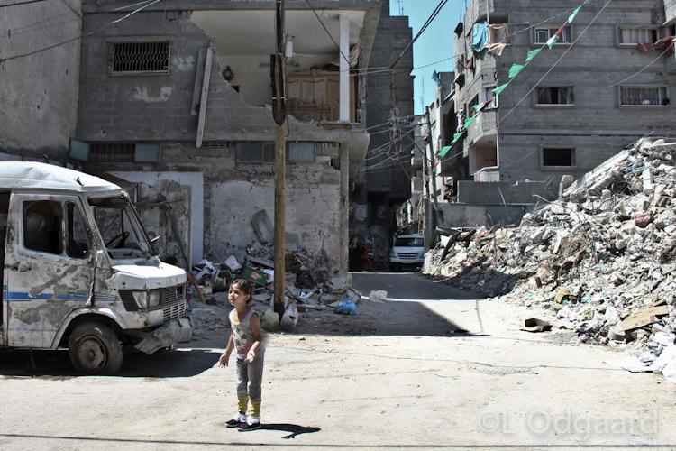 Girl standing under destroyed apartment, Gaza