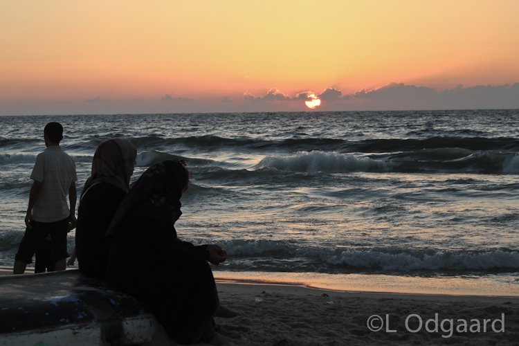 Palestinian women looking at sunset on Gaza beach after ceasefire
