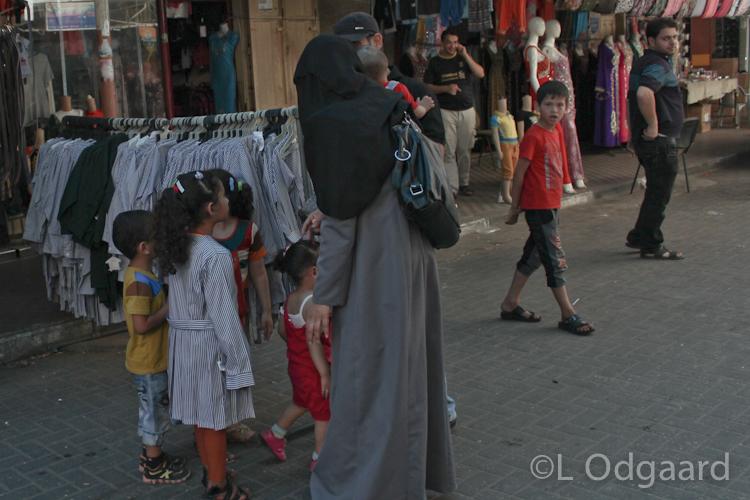 Girl trying on new school uniform in Gaza