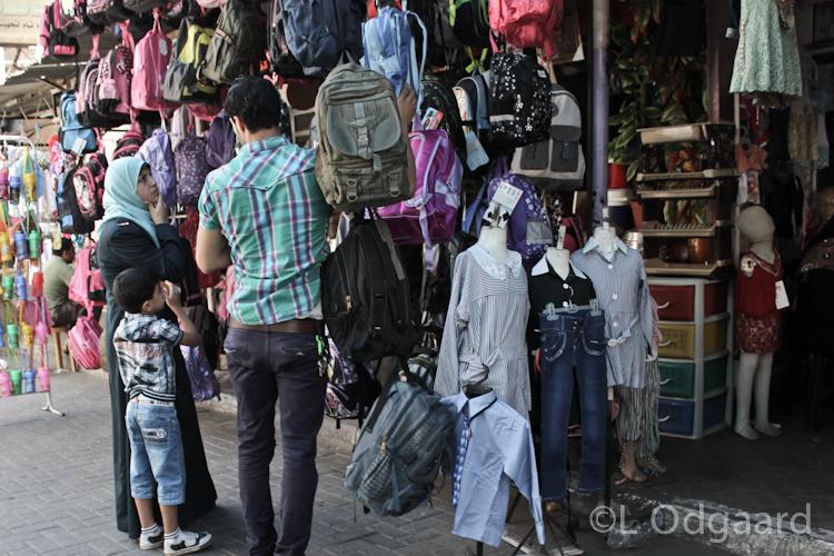 Gazan woman and boy shopping school bag