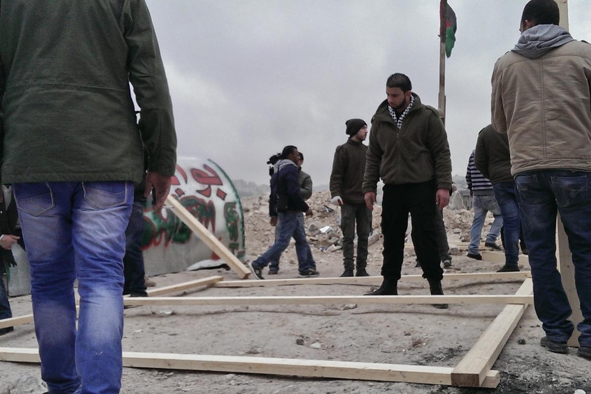 Palestinian activists build a tent at the protest camp, Bawabet Al-Quds