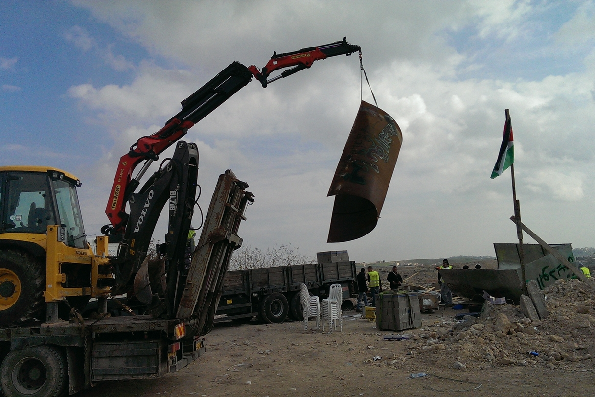 The tin shack is lifted onto a truck with the tent and building materials in the camp