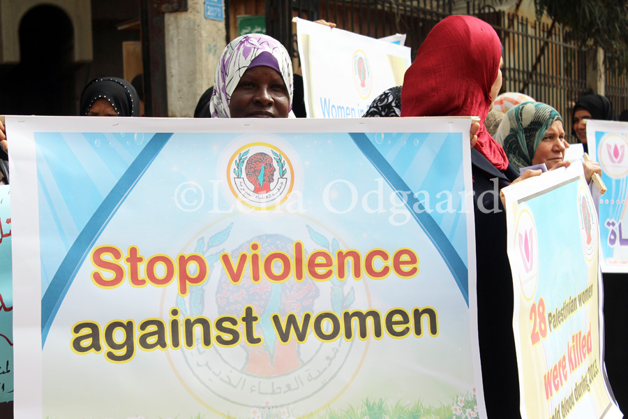 Gazan woman holds sign against femicide