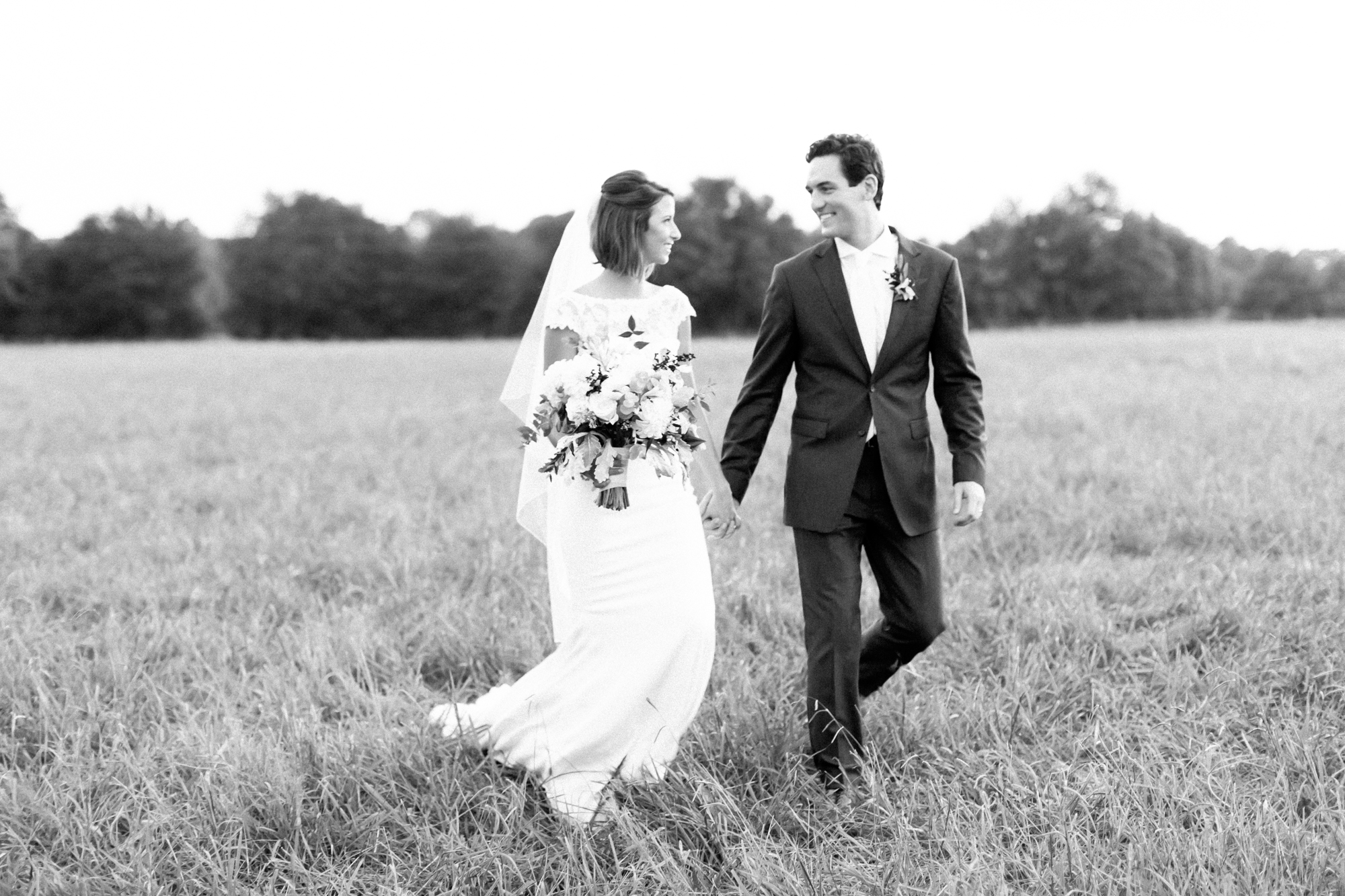 bride and groom walking on field in black and white
