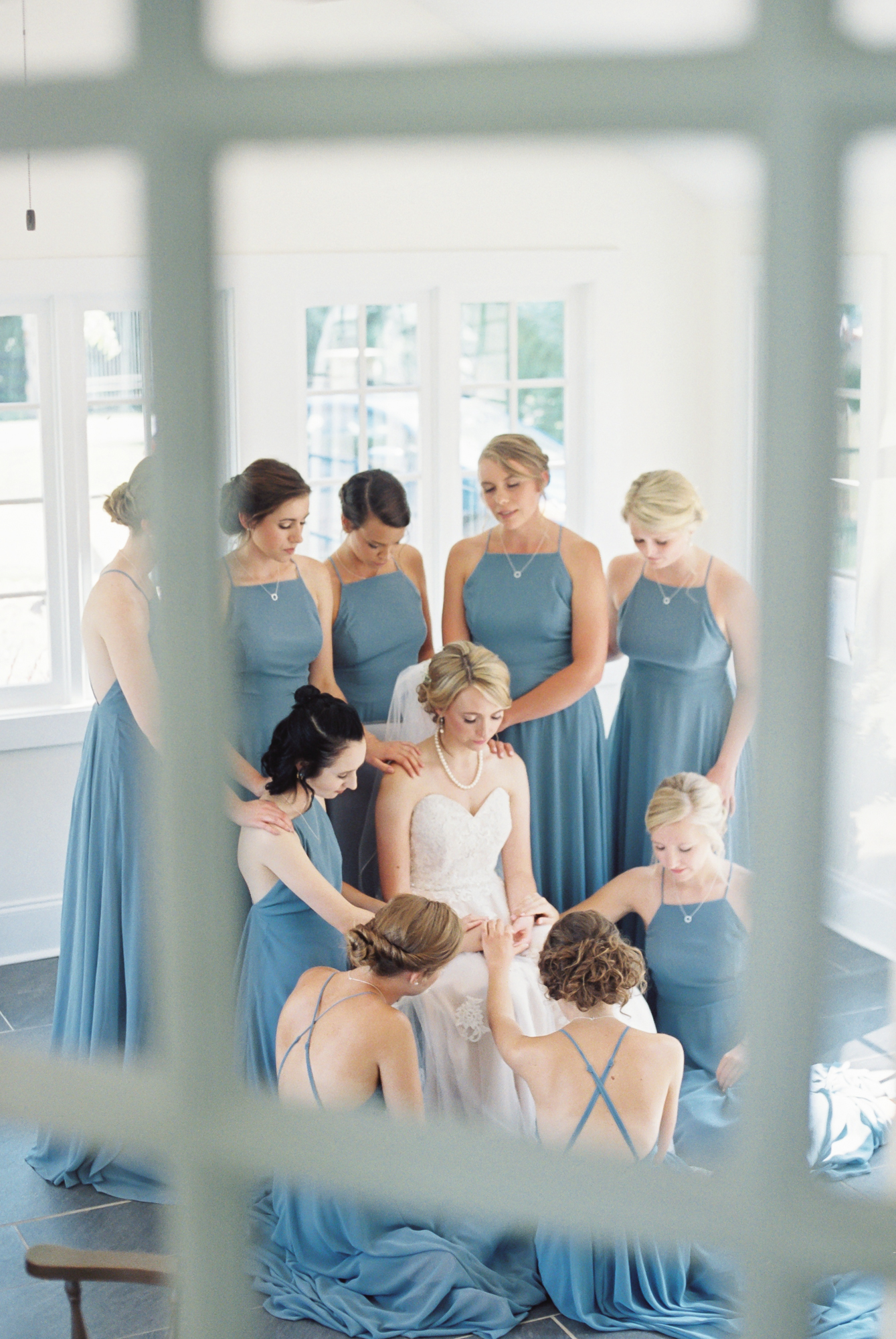 bridesmaids pray over bride