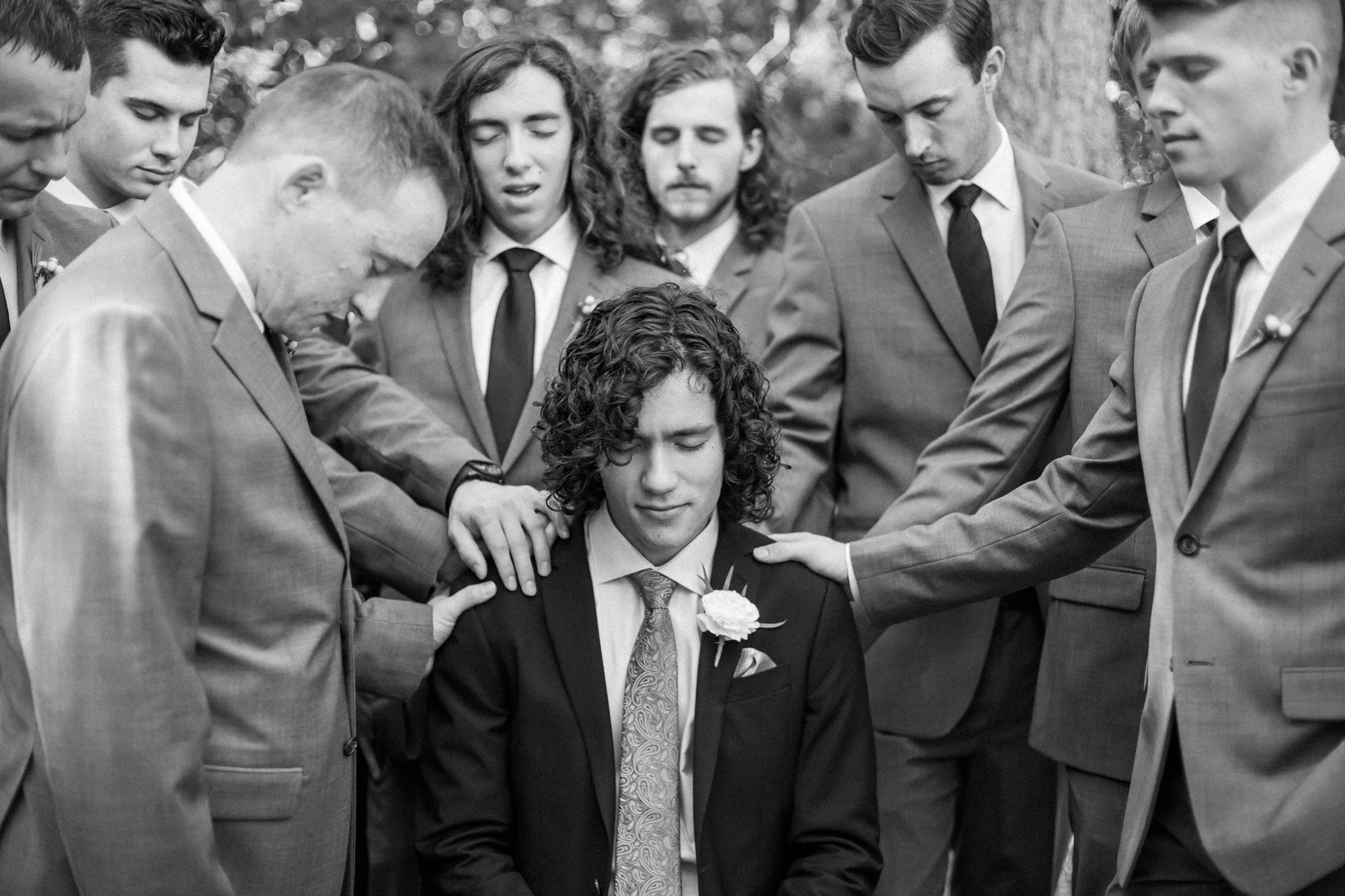 groomsmen pray over groom