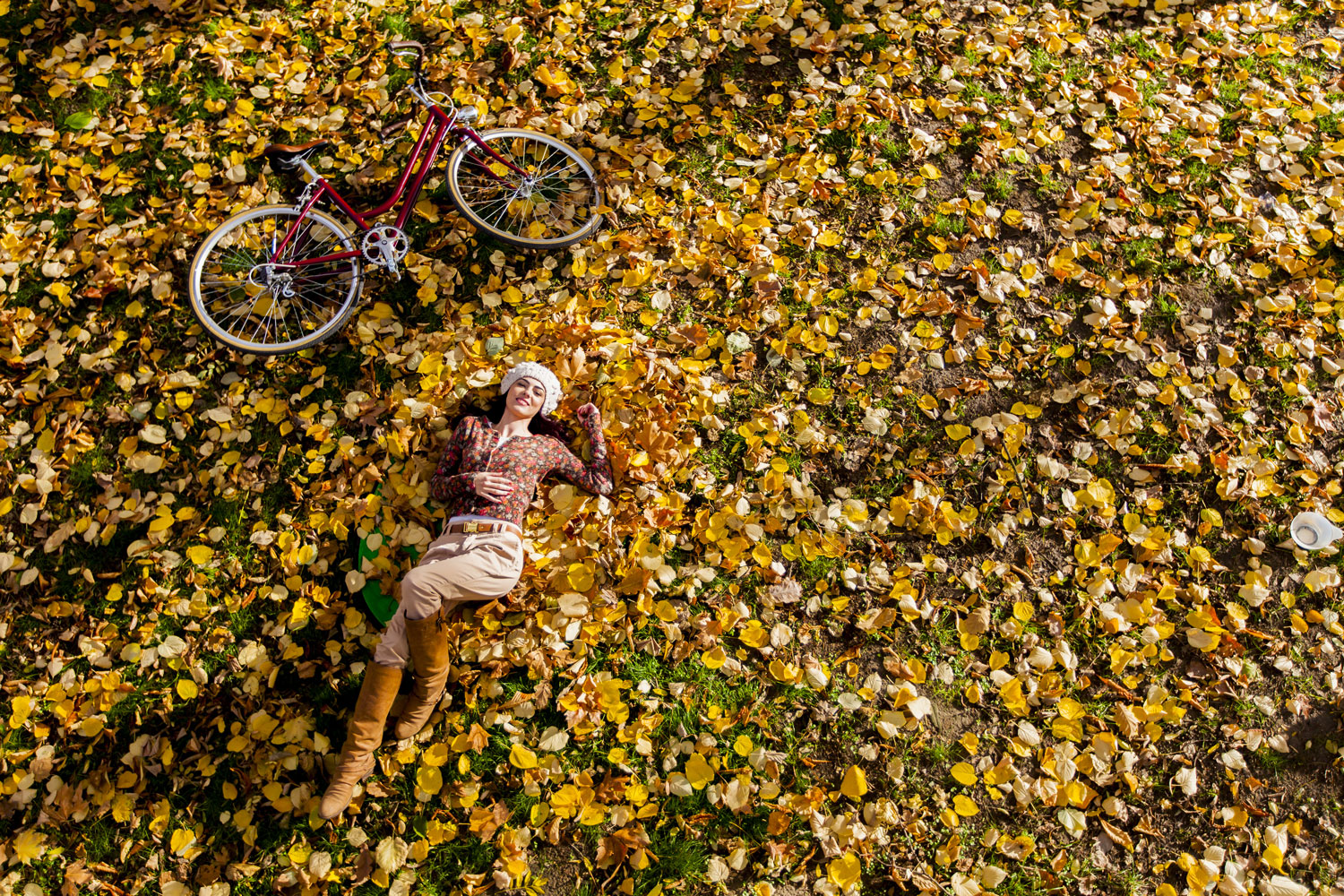 Girl lying in the leaves next to vintage bicycle. bella magazine