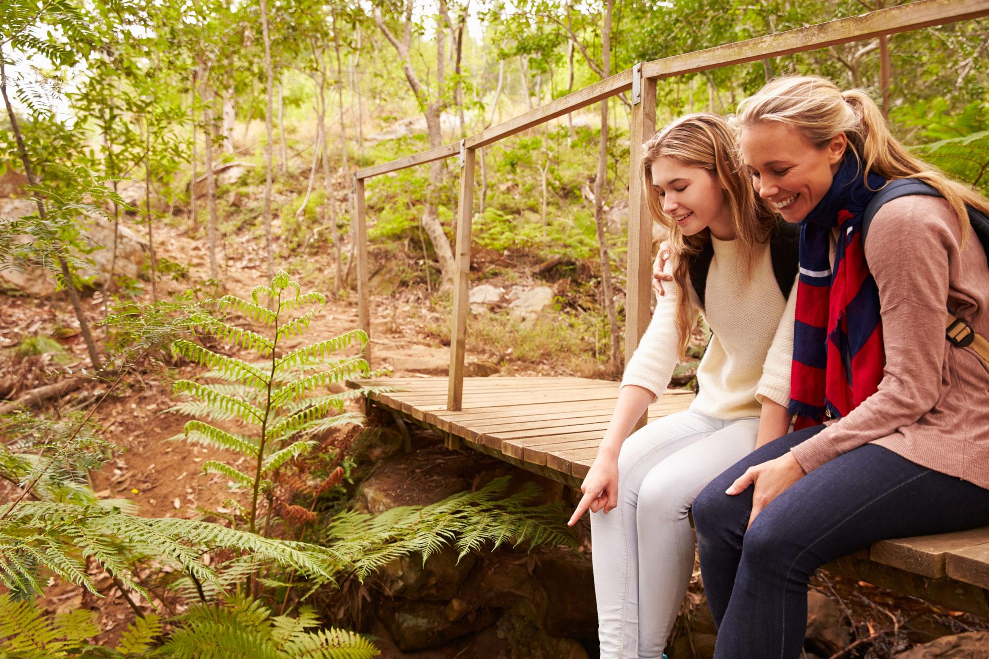 Mum and daughter talking sitting on a bridge.