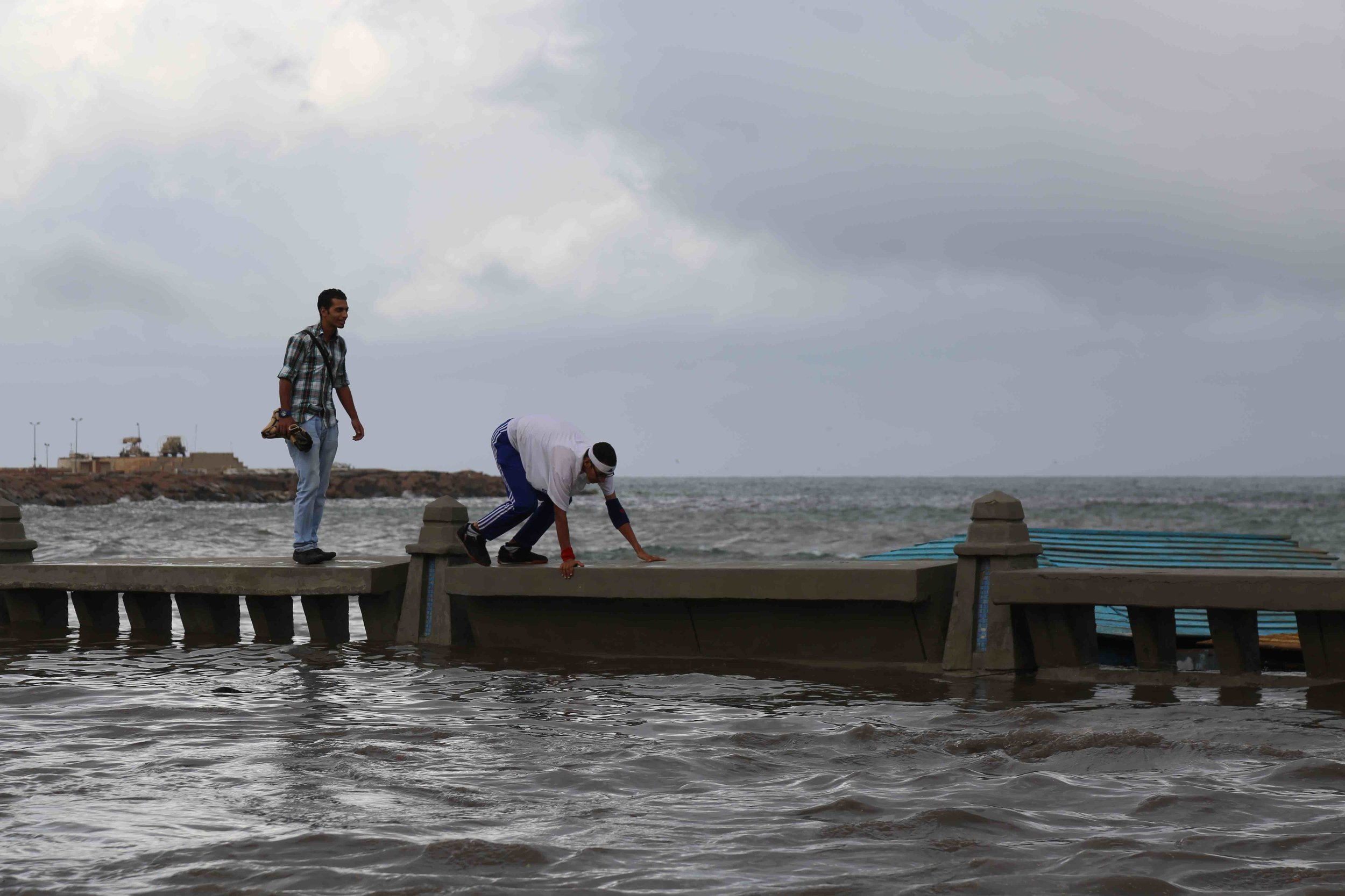 People walking ontop of a submerged wall along the 'corniche' road.