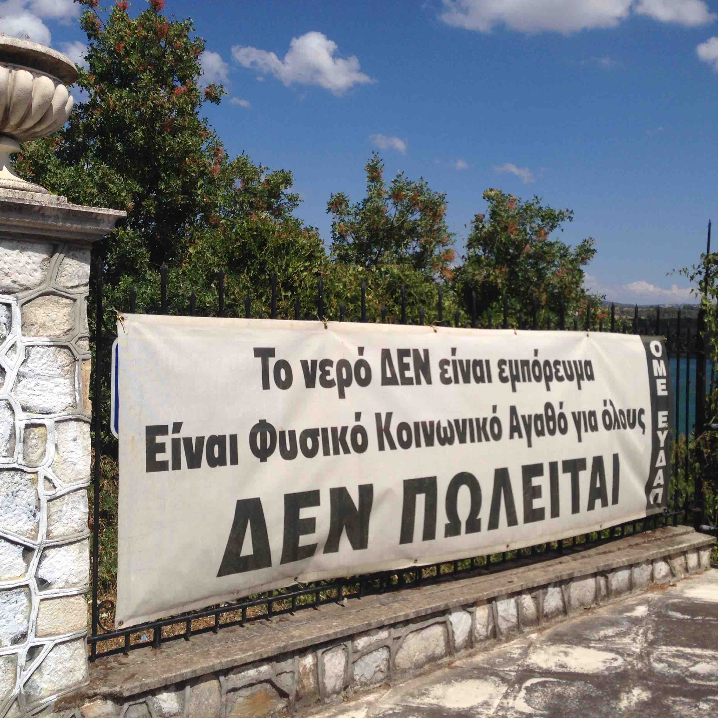"A banner placed by the syndicate of employees of EYDAP at the Dam site, ""Water is NOT a commodity, it is a natural and common resource for all, IT IS NOT FOR SALE"", in protest to the threat of the privatization of the Athens municipal water supply.  Photo: Melina Nicolaides, 2016."