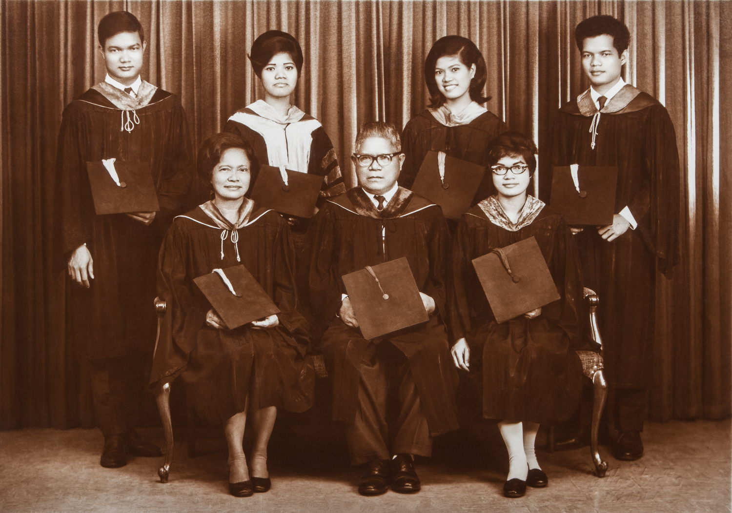 This digital image file is a fully restored studio portrait from a sepia-toned silver gelatin print showing the family of my maternal grandparents in their graduation attire. This photograph was taken on December 25, 1968 at the legendary Rialto Studio in Escolta, Manila (Philippines). From left to right, standing: Judge Isauro Balderian; Dr. Melania B. Domingo; Delia B. Pestaño, RPh; Engr. Ludovico Balderian; Seated: Mrs. Imelda M. Balderian, M.A.Ed, Atty. Cornelio Balderian, Erlinda B. Guevarra, J.D.