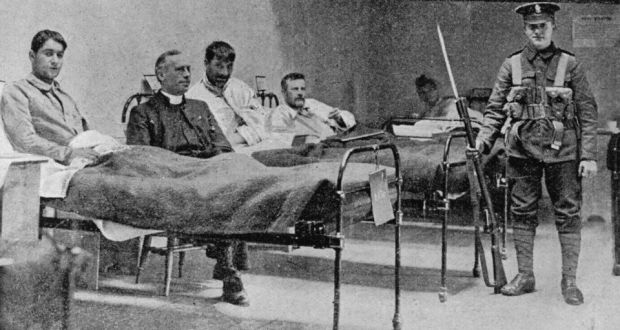 A British soldier stands guard at the bedside of wounded rebels, 1916.