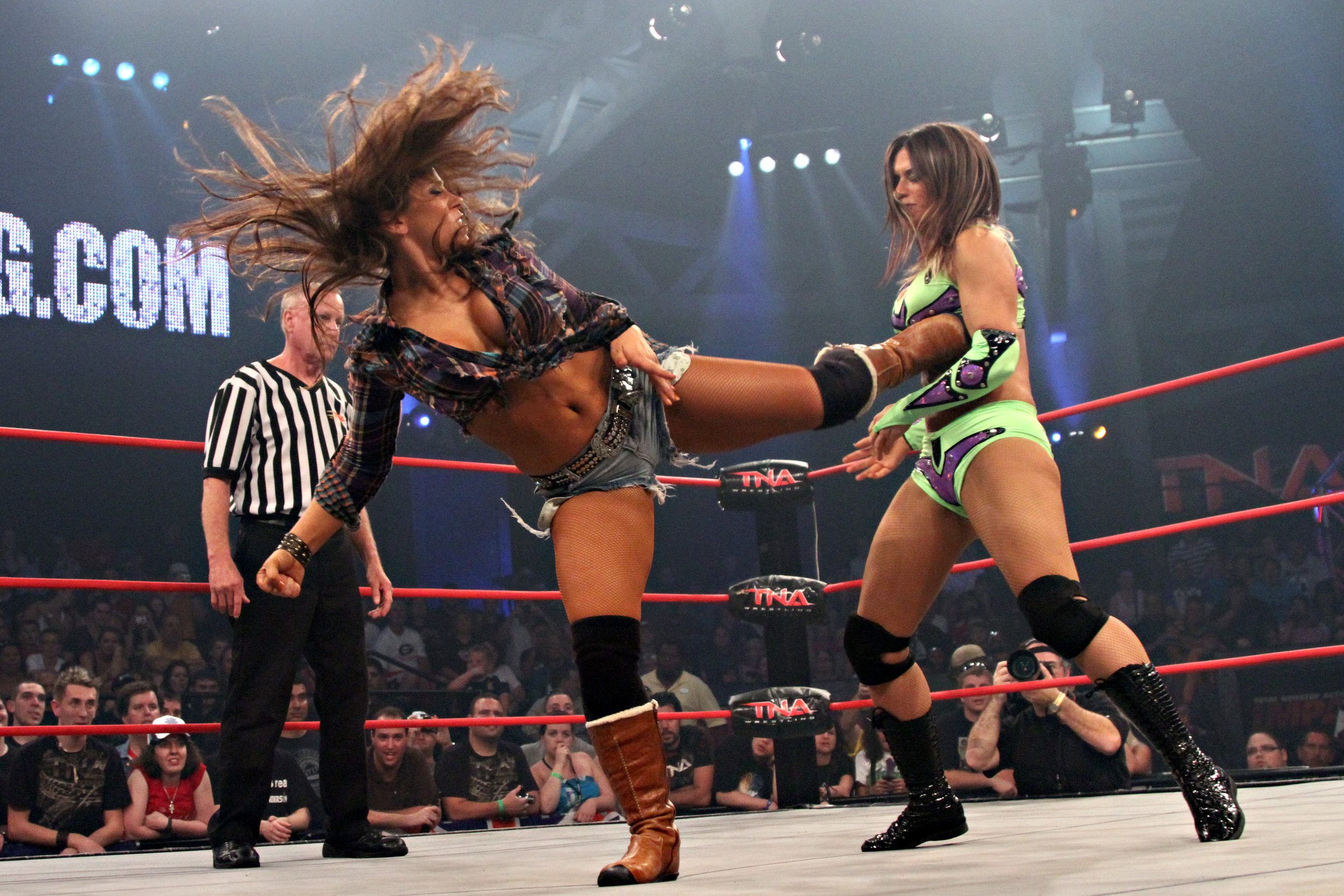 Mickie James delivers a spinning back kick to Sarita - Photo courtesy of Lee South and TNA Entertainment LLC.jpg