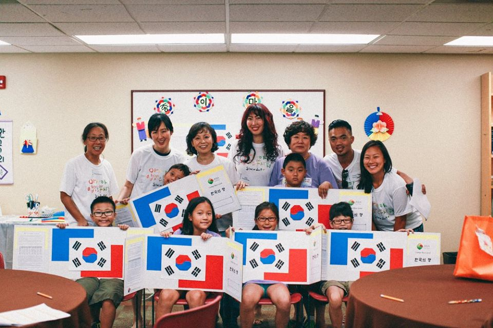 Children and adults adopted from Korea, along with Korean-American volunteers, are showing off Taegukki that they made with Sylvia Kim of the Washington Korean Paper Folding Institute