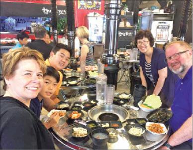 Korean adoptees and Their parents on the 'Korea Bridge Tour' enjoying Korean food.