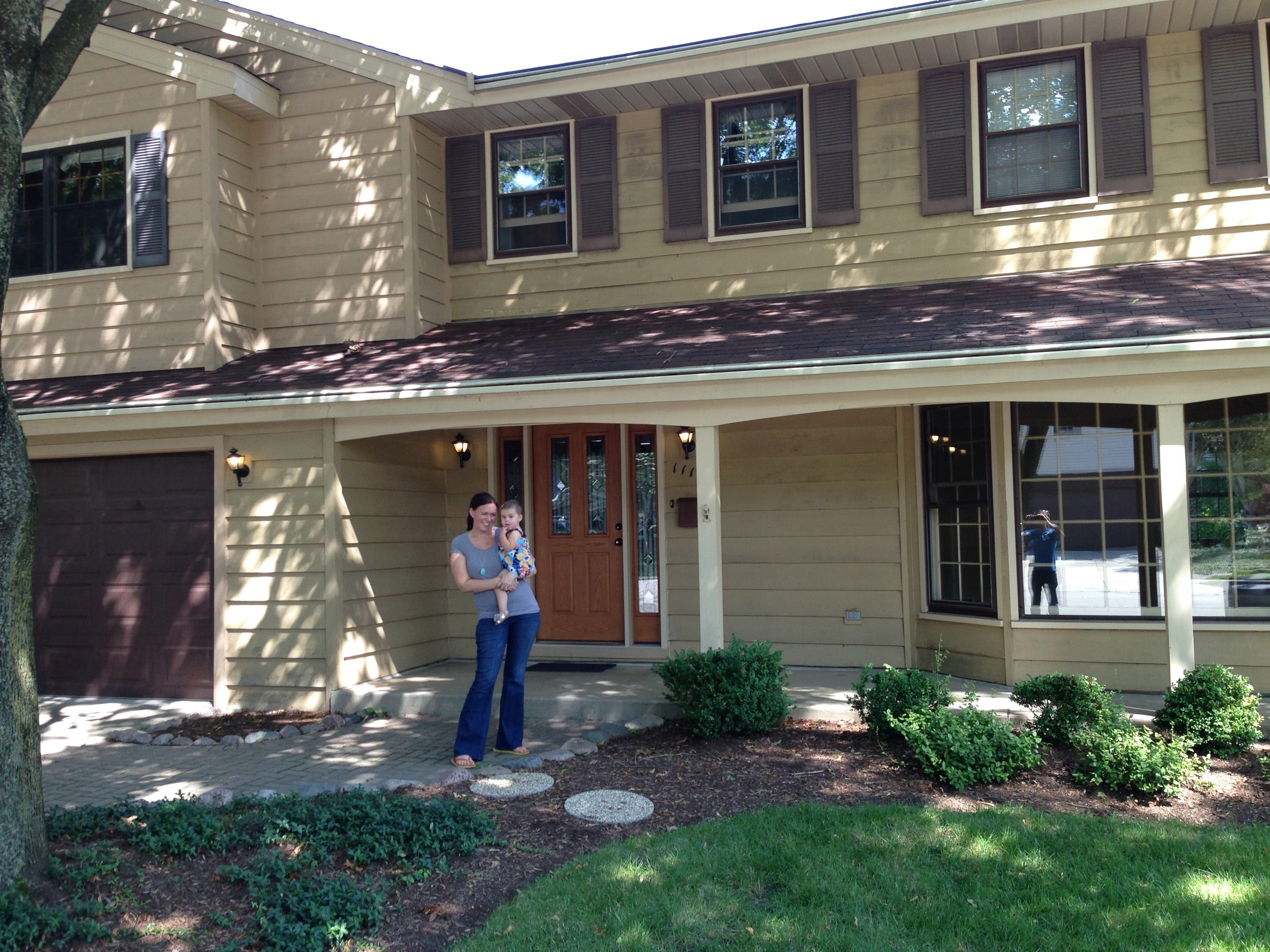 Me and Maddie standing outside our new house on closing day.