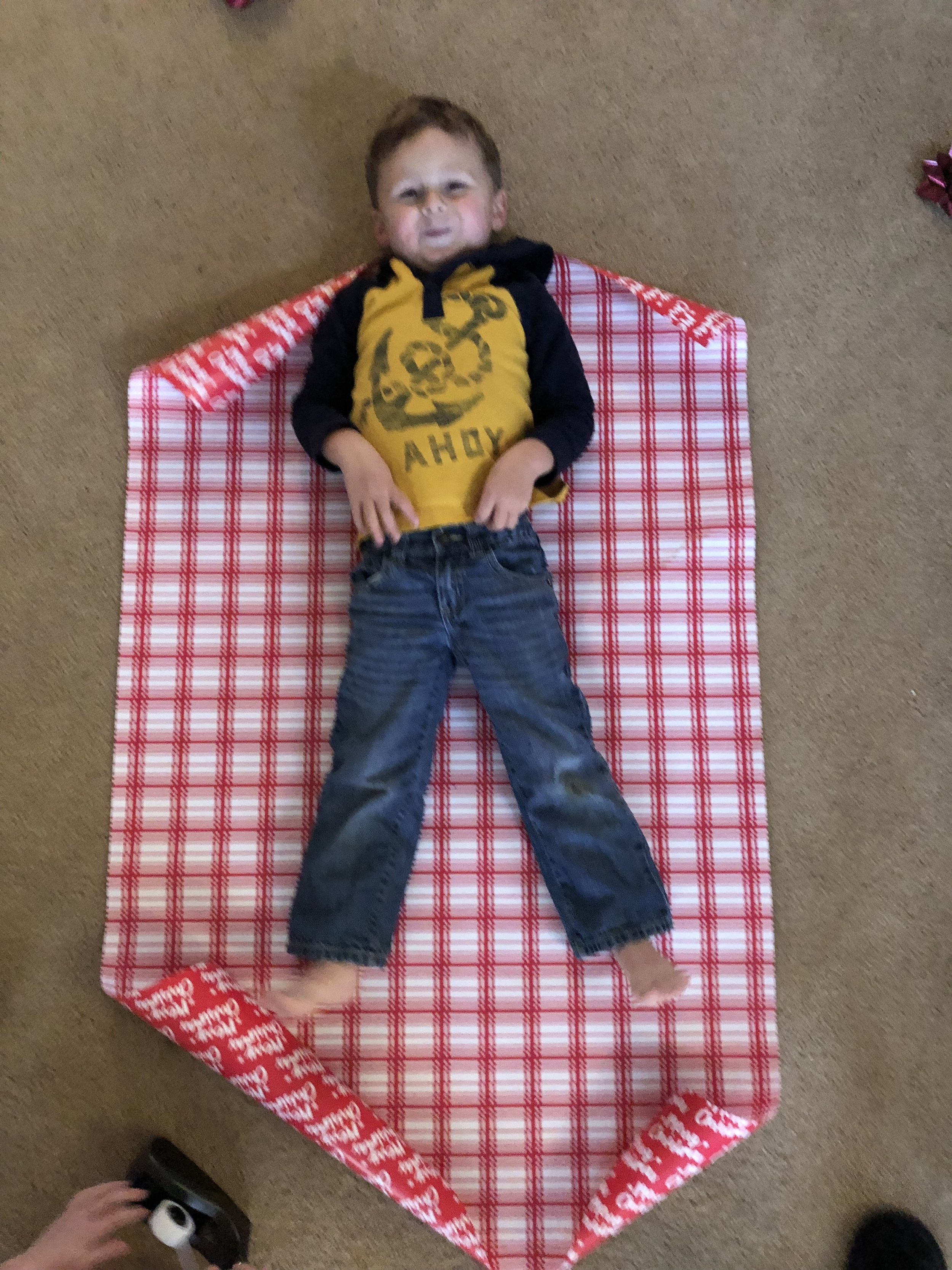 We were having so much fun, I didn't realize my photos were blurry until after we were out of wrapping paper. Whoops! This still gives you a general idea - my son did not want his head wrapped so his neck was at the edge of the paper.