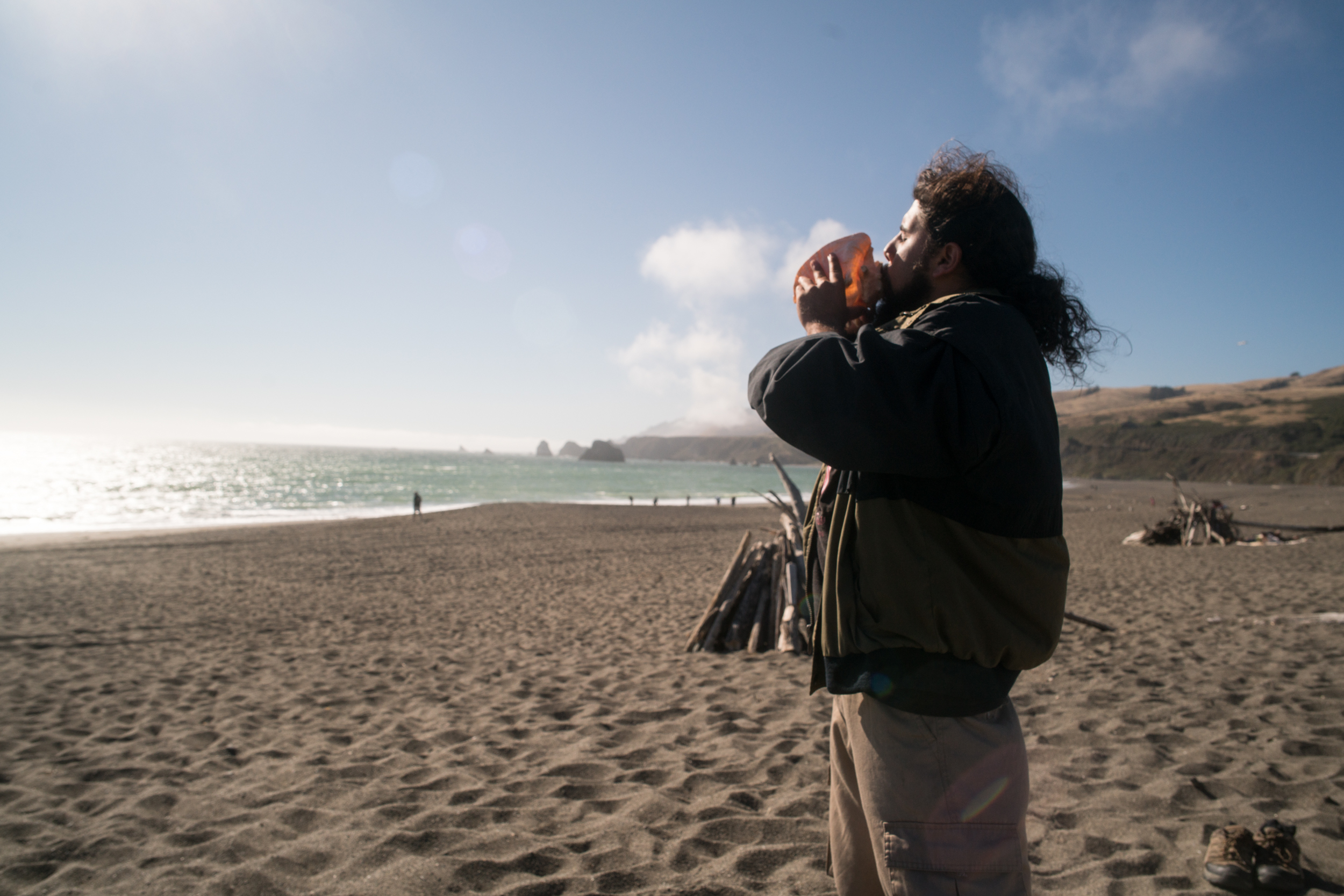 A young man from the Guardians of the Waters Native Youth program blows a conch shell to greet the Pacific Ocean