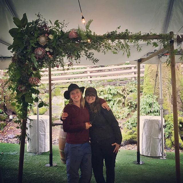 One year ago today✨✨✨ After driving through, and designing through, the pouring rain, these two #nbfc goofs were darn proud of the beauty their hard work and collaboration had created. Flowers and foliage (excluding the proteas, which were #cagrown) sourced locally from #sonomacounty growers. #communityovercompetition  Florals by @fullbloomflowerfarm & @joleeblooms