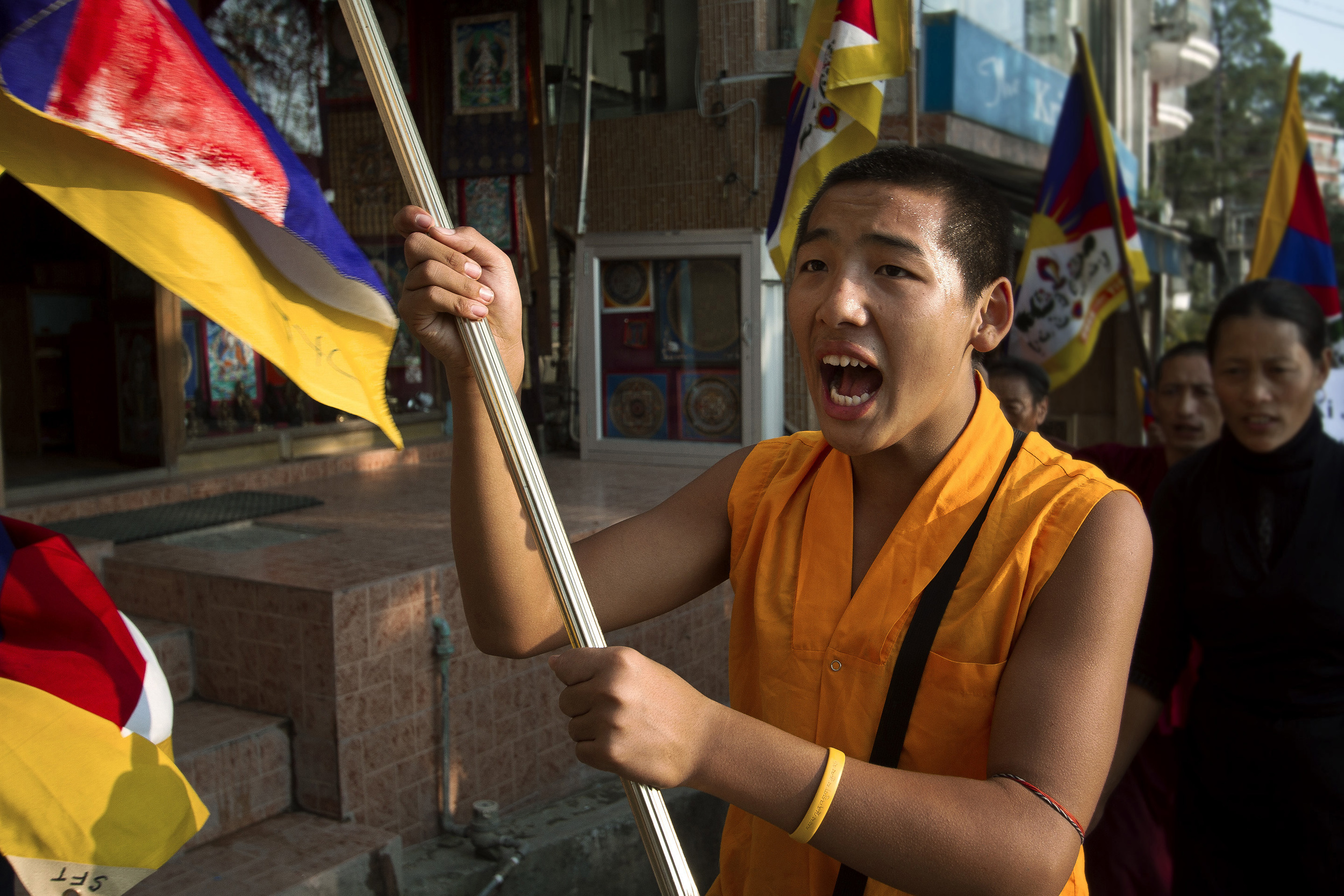 8 November, 2012 - McLeod Ganj   A young nun waves the Tibetan flag, outlawed in Tibet, during the largest of the self-immolation protests in McLeod Ganj.