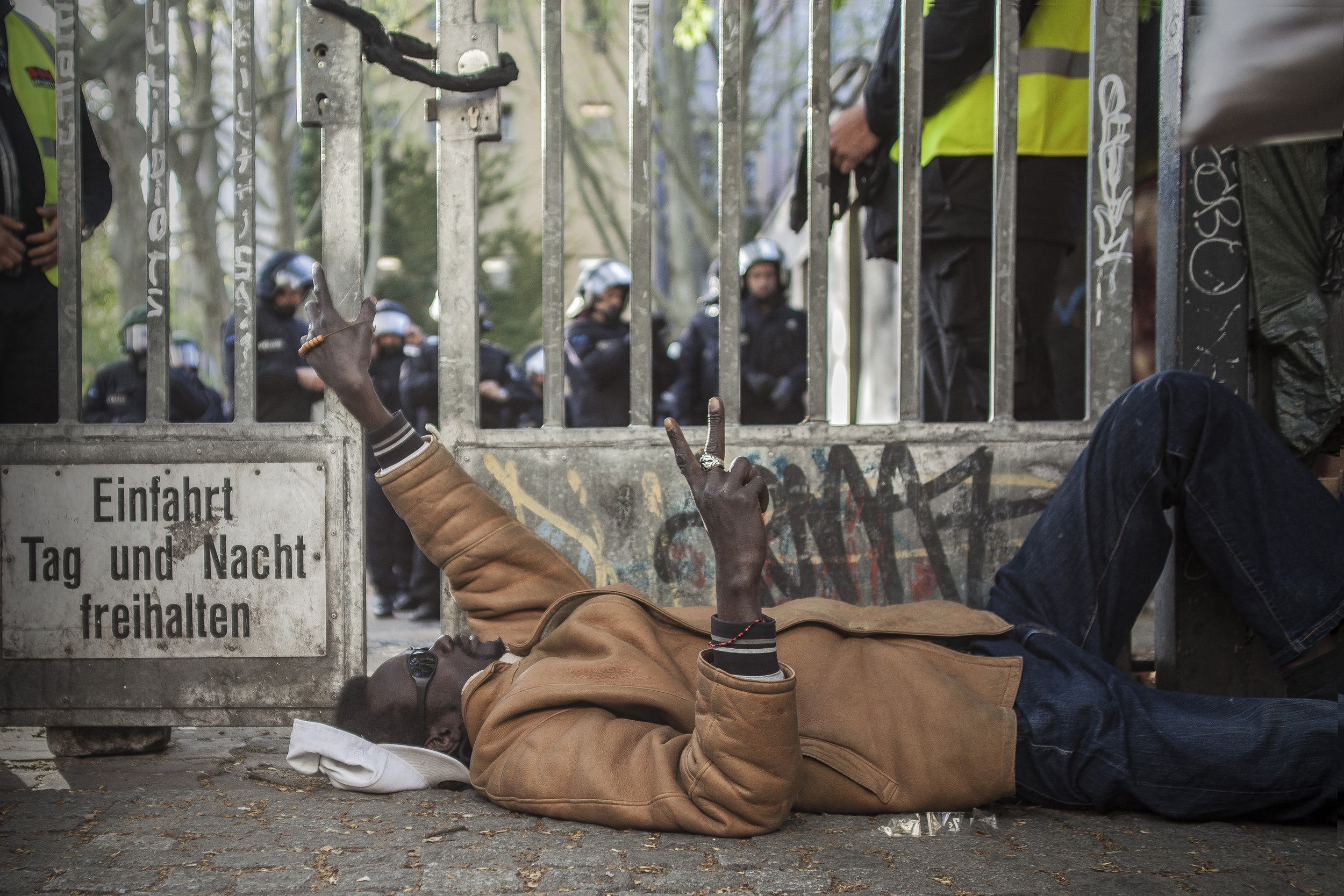 1 May, 2015 - Berlin, Germany   Protester by the gates of the Gerhart-Hauptmann Schule. The abandoned building was formerly occupied by African asylum seekers until they were forcibly removed one month prior. In anticipation of the annual massive May 1st demonstrations in Berlin police accompanied by service dogs fortified the complex's entrance.