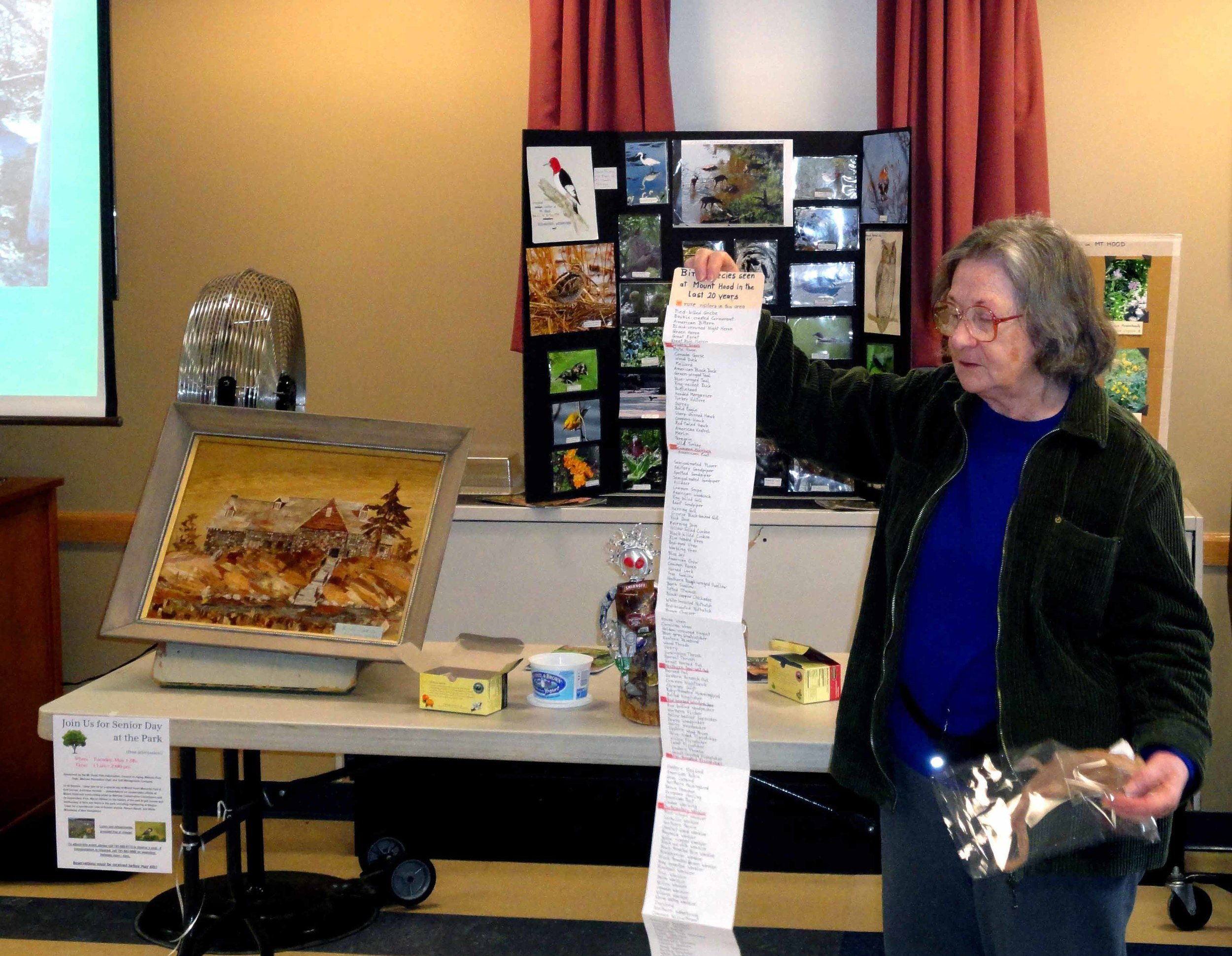 Enge Jewell displaying a list of over 150species of birds seen at Mount Hood Park in a 20 year period. She also displayed pictures of many birds seen at Mount Hood including artwork she created using materials found at the park. The framed picture shown above she made by assemblingdifferent pieces of birch bark found on the ground at the park.